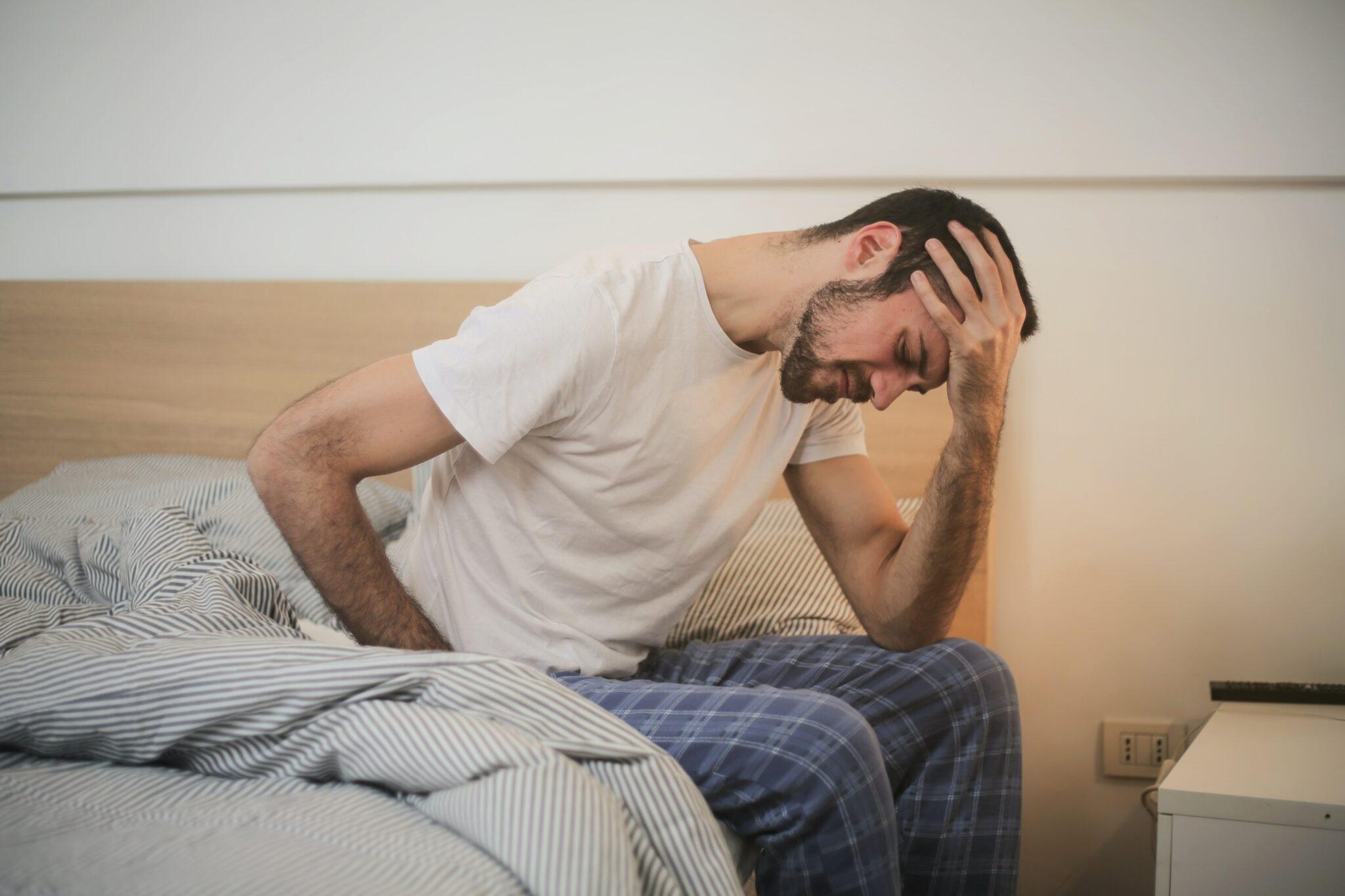 Ein Mann sitzt auf dem Bett und hält sich müde den Kopf.