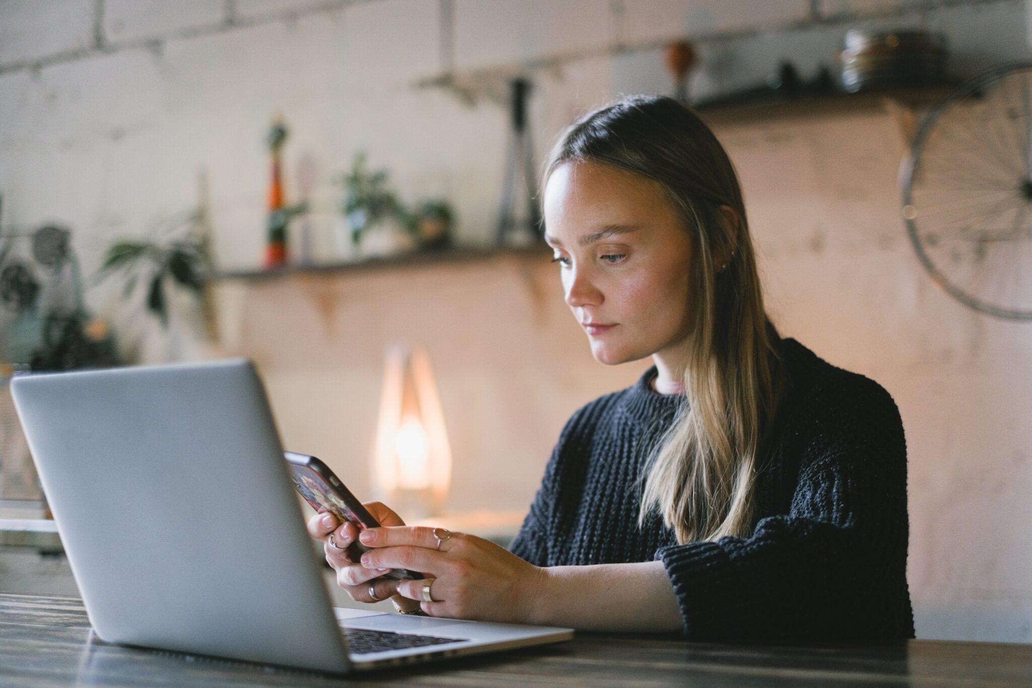 Eine Frau sitzt vor einem Laptop und benutzt ihr Handy