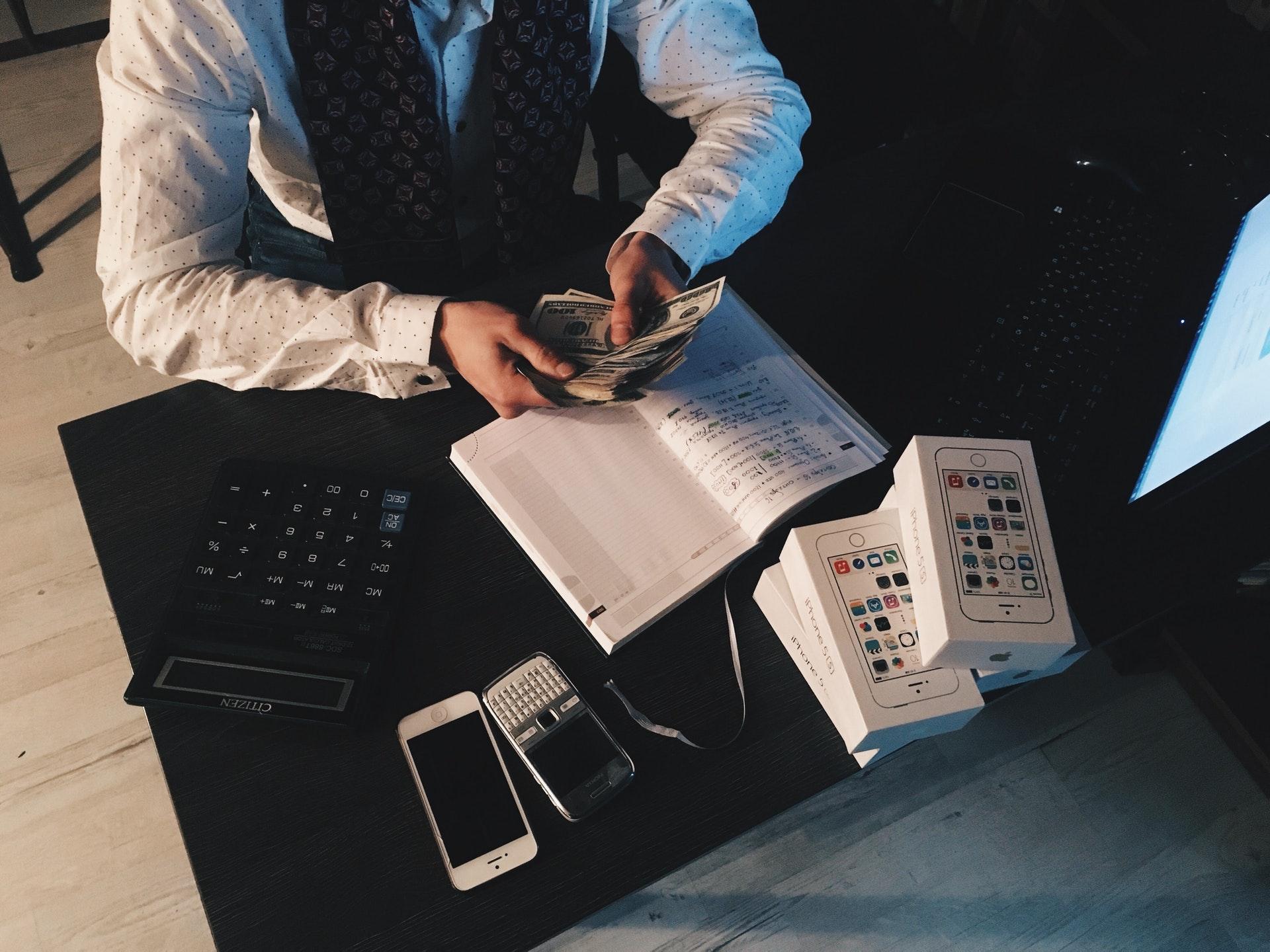 Ein Mann zählt Geld an seinem Schreibtisch.