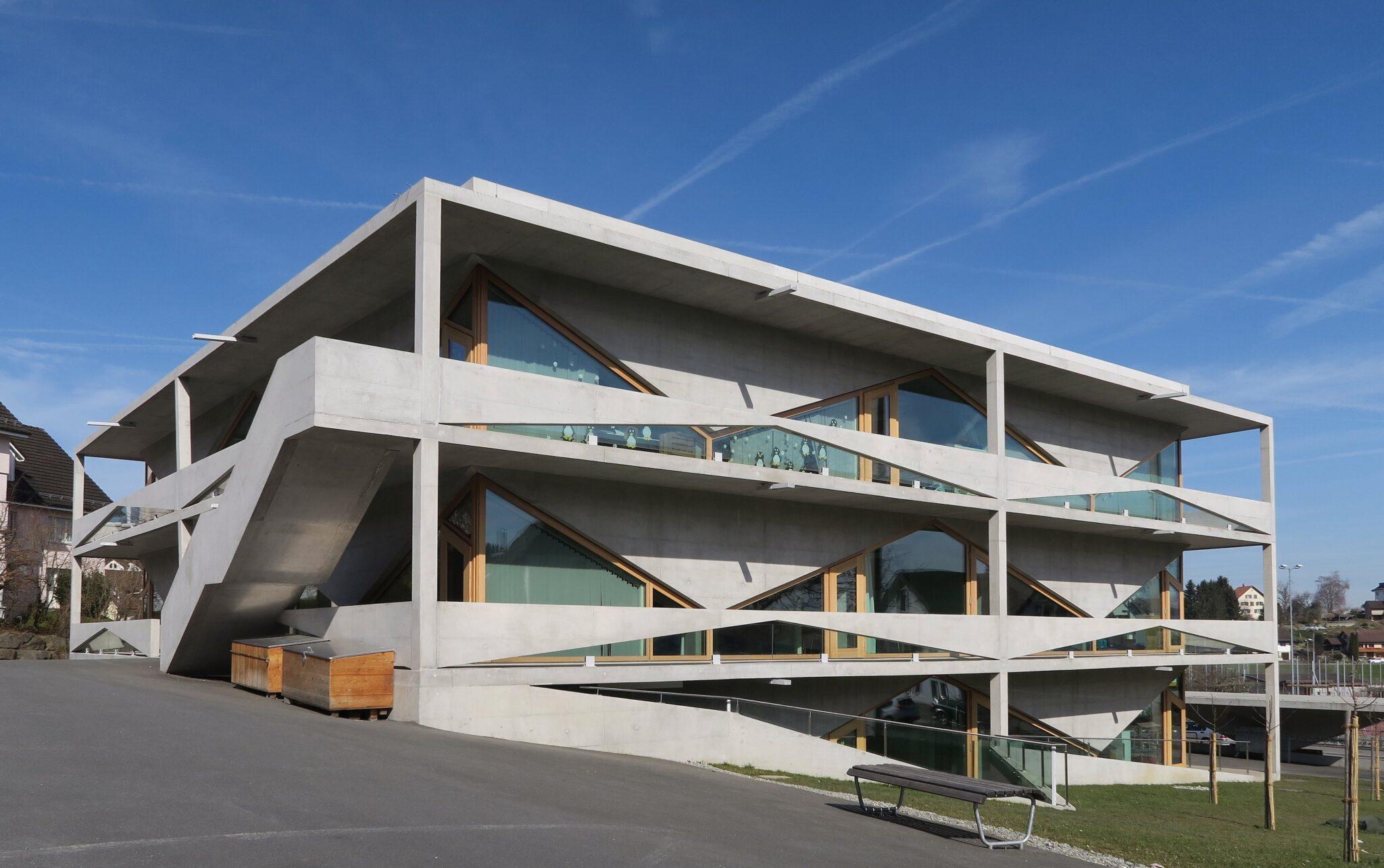 Aussenansicht von der seite oder von hinten des modernen Schulgebäudes aus Beton.