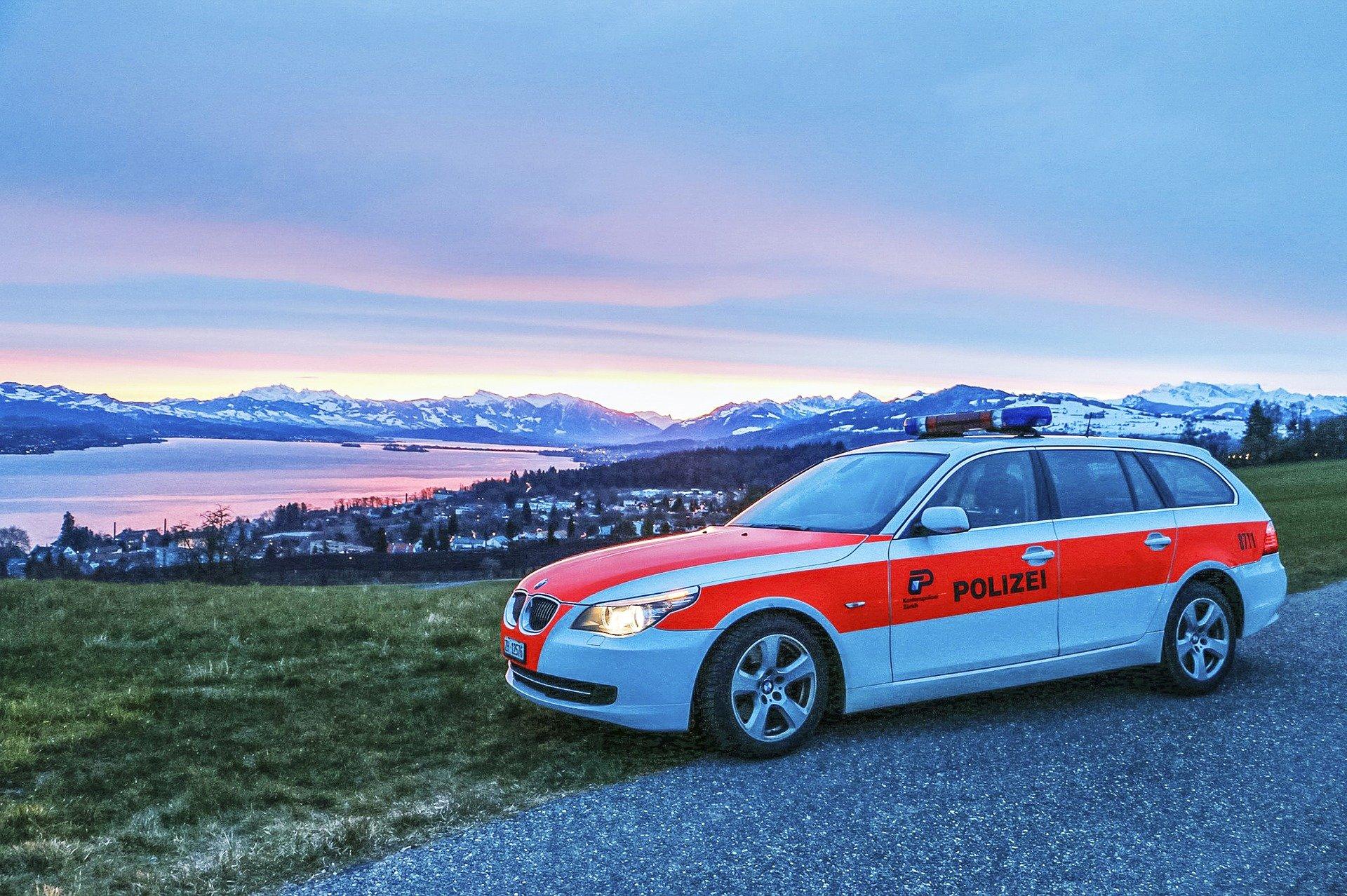 Ein Polizeiauto in weiss und orangerot vor einem See bei Sonnenuntergang.