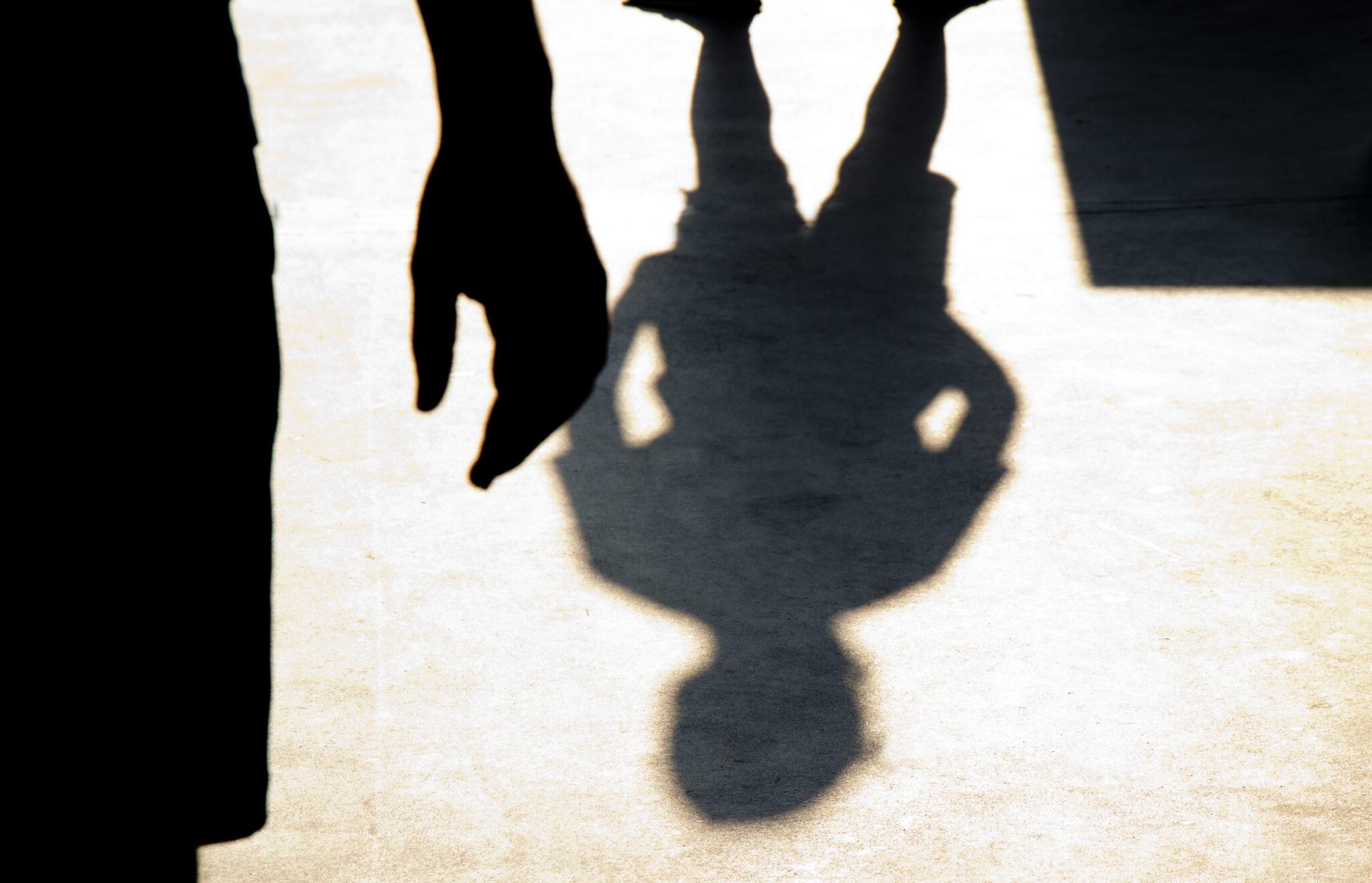 Schatten eines Jungen und Silhouette einer Hand im Vordergrund