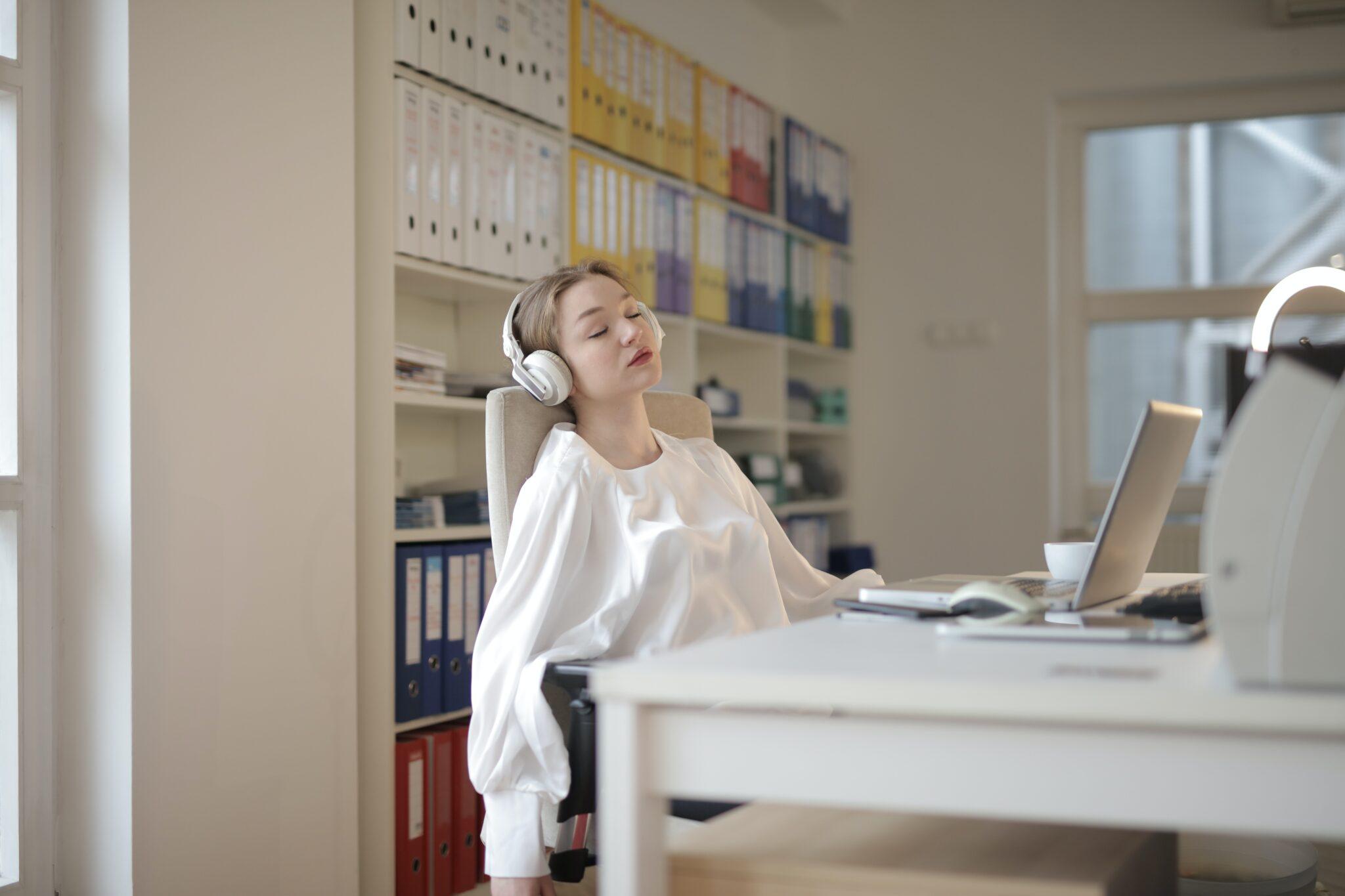 Eine Frau hört am Arbeitsplatz Musik auf Kopfhörern