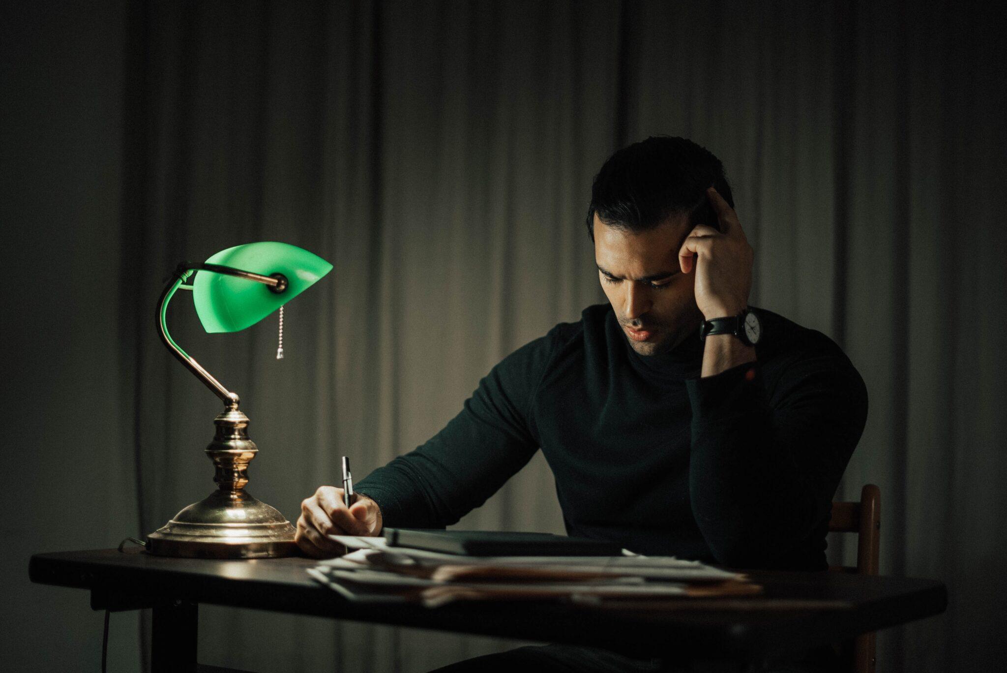 Ein Mann sitzt nachts arbeitend am Schreibtisch