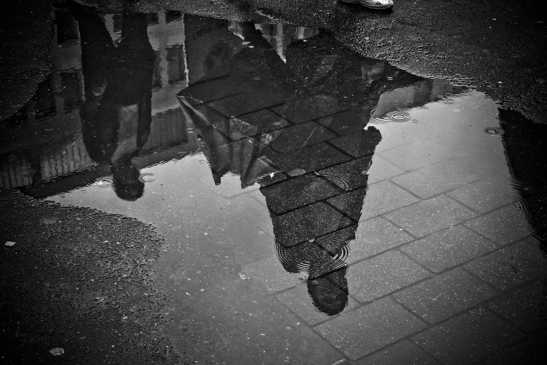 Ein Schwarz-Weiss-Foto von Menschen, deren Umrisse sich in einer Pfütze spiegeln.