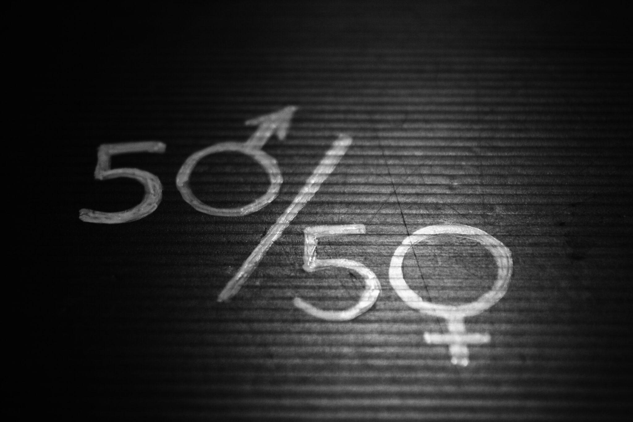 50/50 mit weiss auf dunkles Holz geschrieben. Die 0 ist jeweils das Symbol für männlich und weiblich