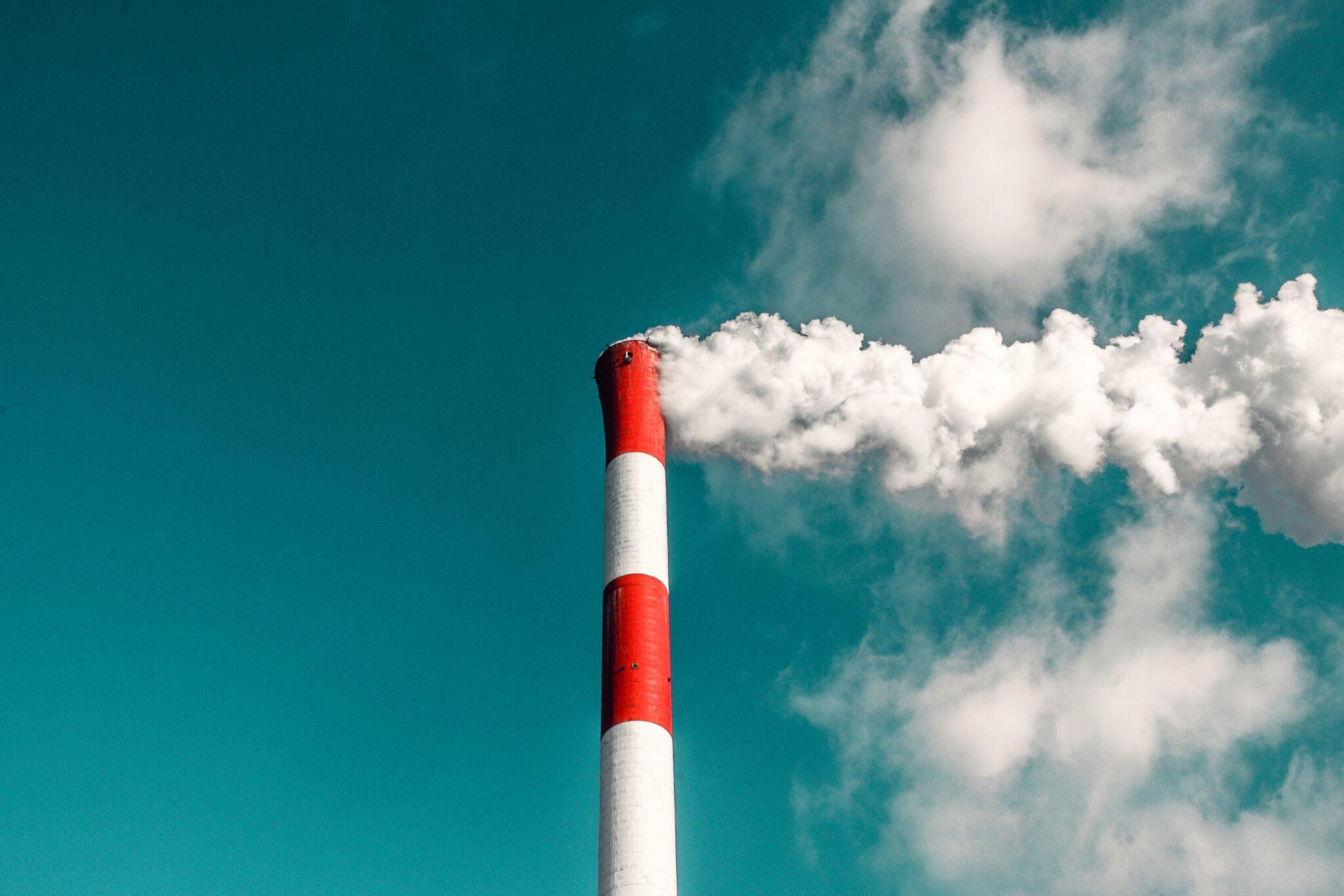 Ein rot-weisser Industrieschornstein, aus dem Rauch kommt