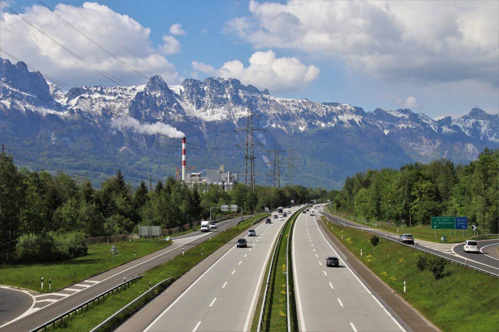 Blick auf die Autobahn bei Buchs mit Bergpanorama und rauchendem Schlot im Hintergrund.