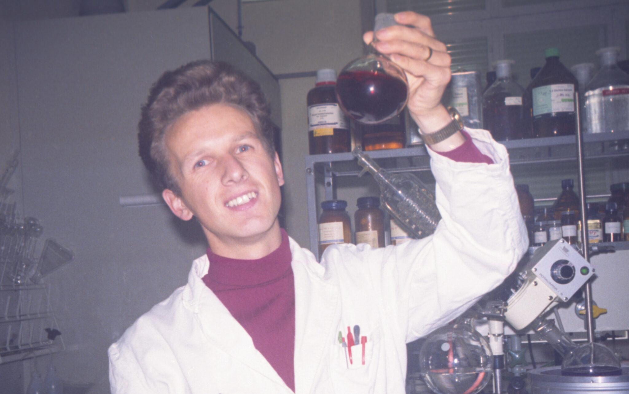 Peter Geissen hält einen Kolben mit roter Flüssigkeit hoch