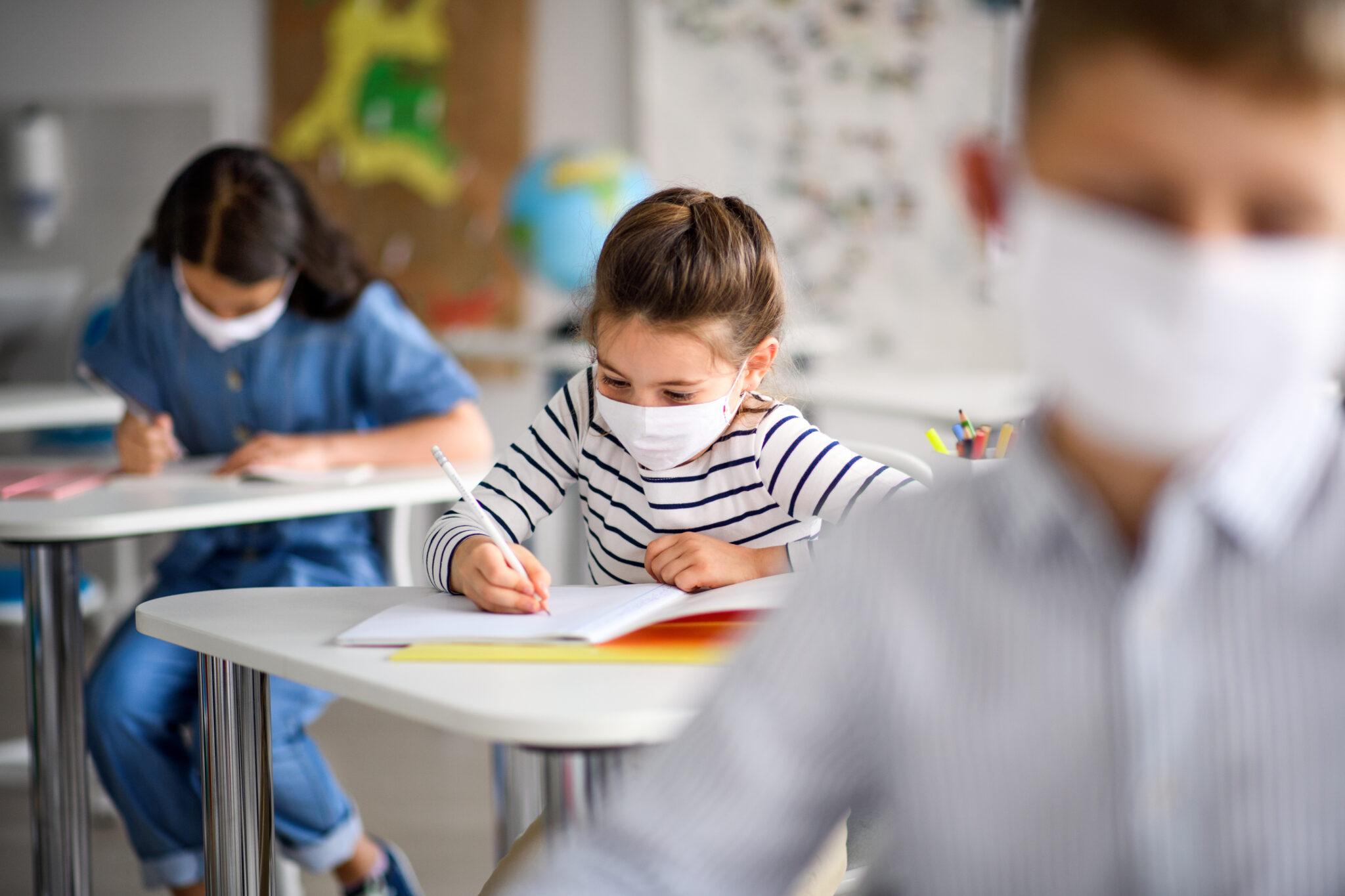 Schüler mit Maske im Klassenzimmer beim Schreiben