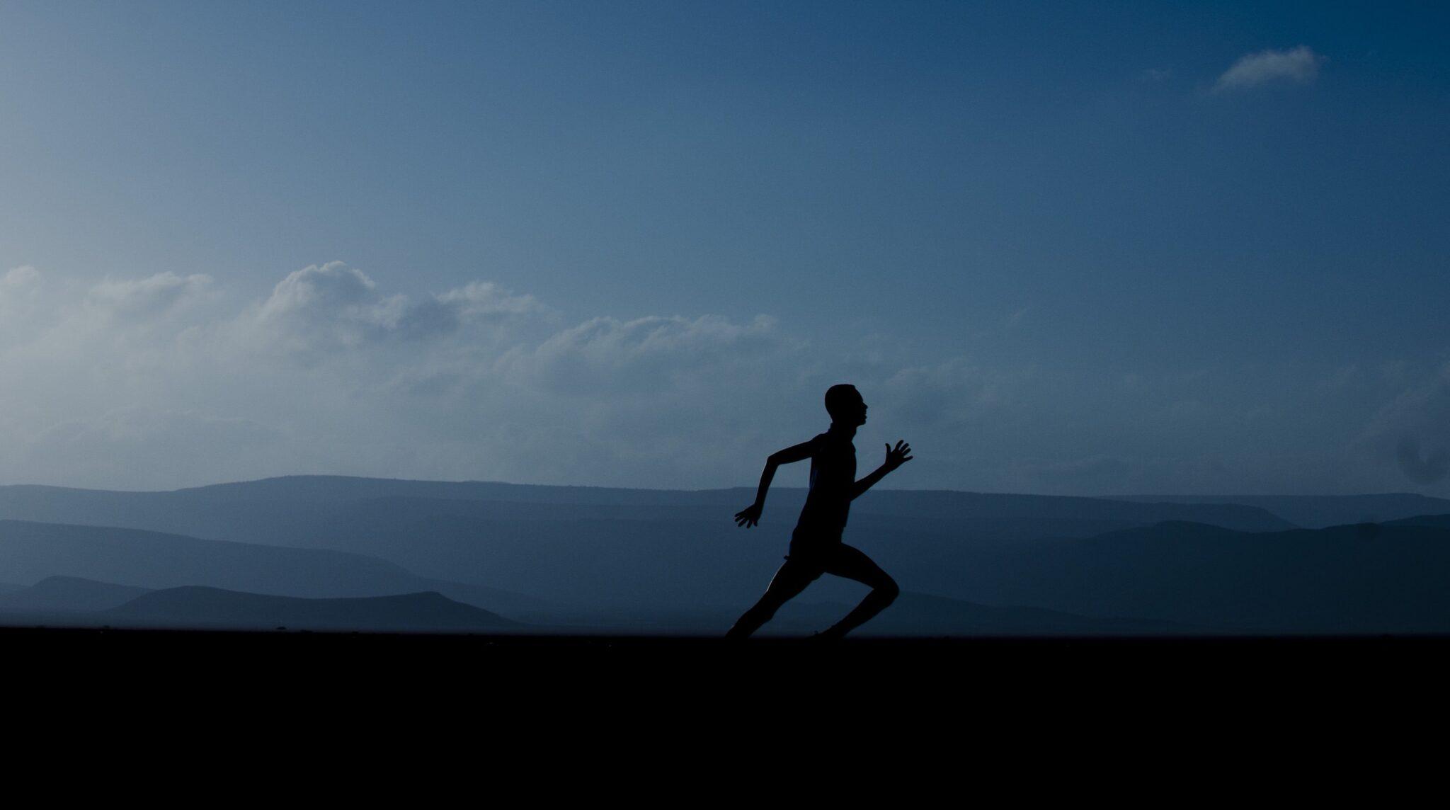Silhouette eines Joggers vor einer weitläufigen Landschaft