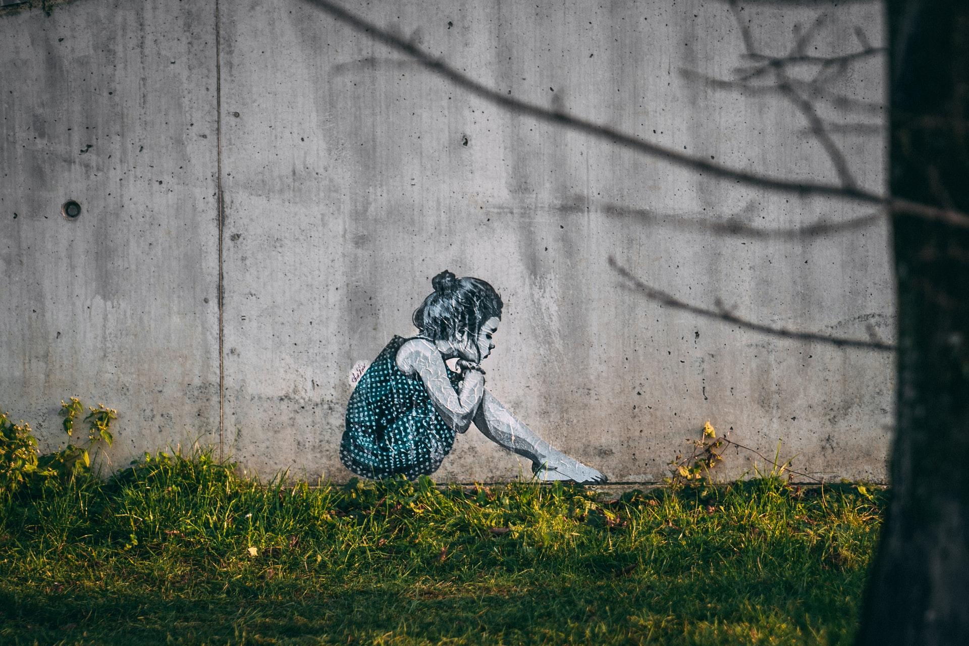 Streetart: Ein Poster von einem Mädchen an einer Mauer vor einer Wiese.