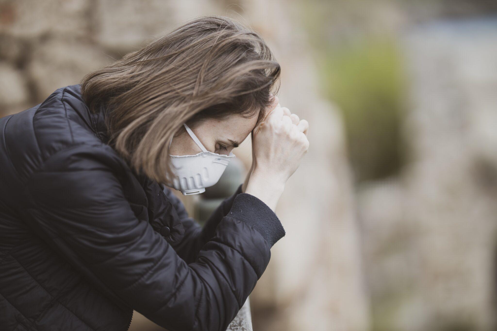 Eine niedergeschlagene Frau mit Atemschutzmaske