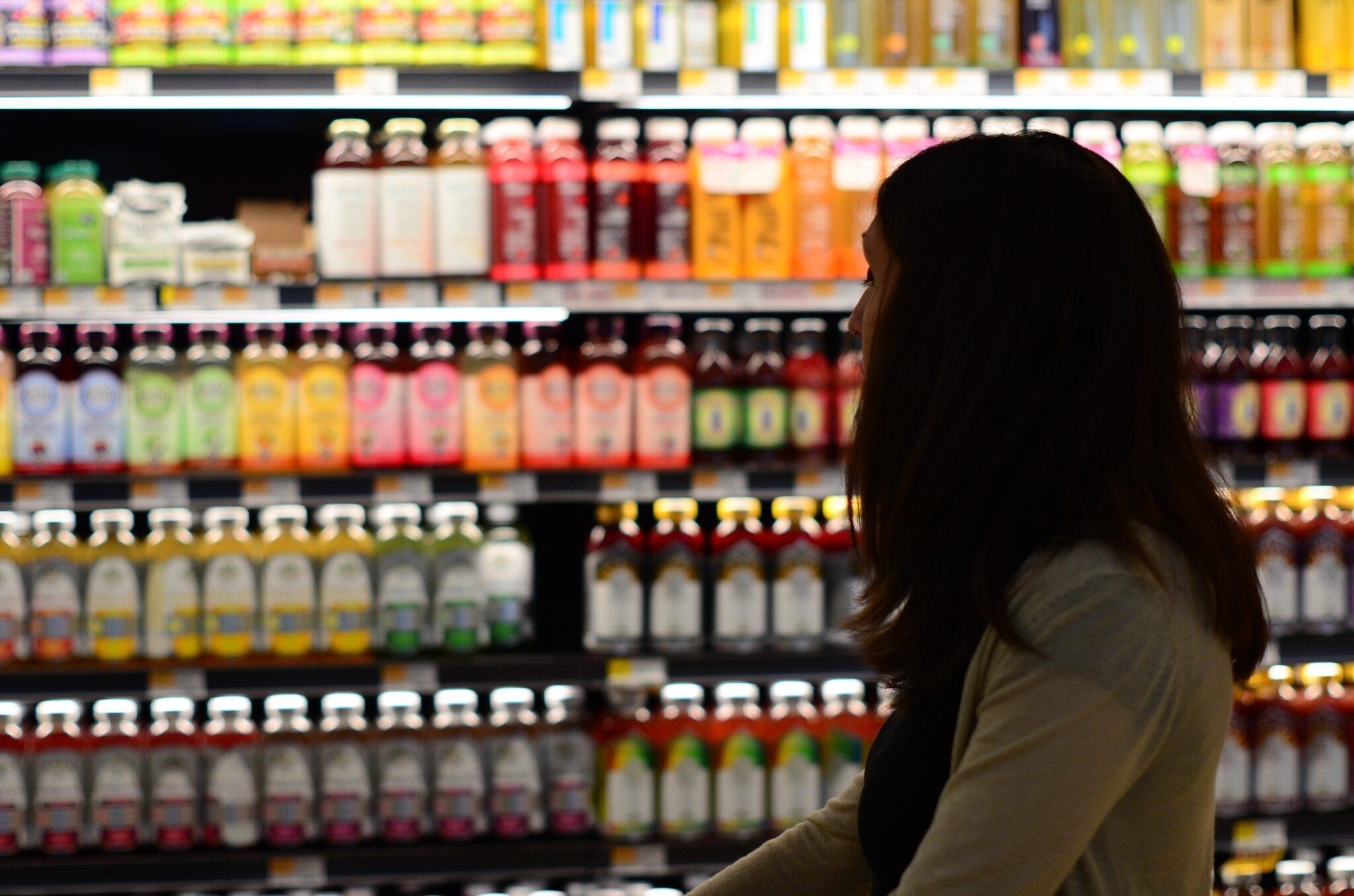 Frau vor einem Getränkeregal im Supermarkt