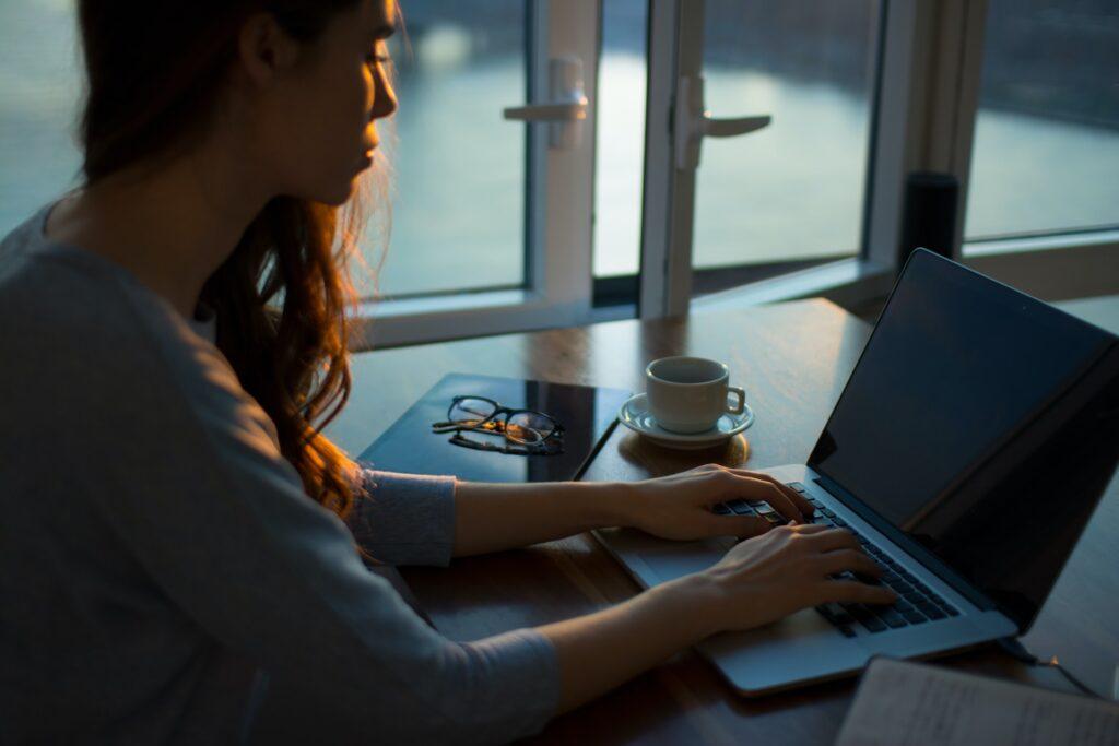 Eine Frau arbeitet sitzend am Laptop.