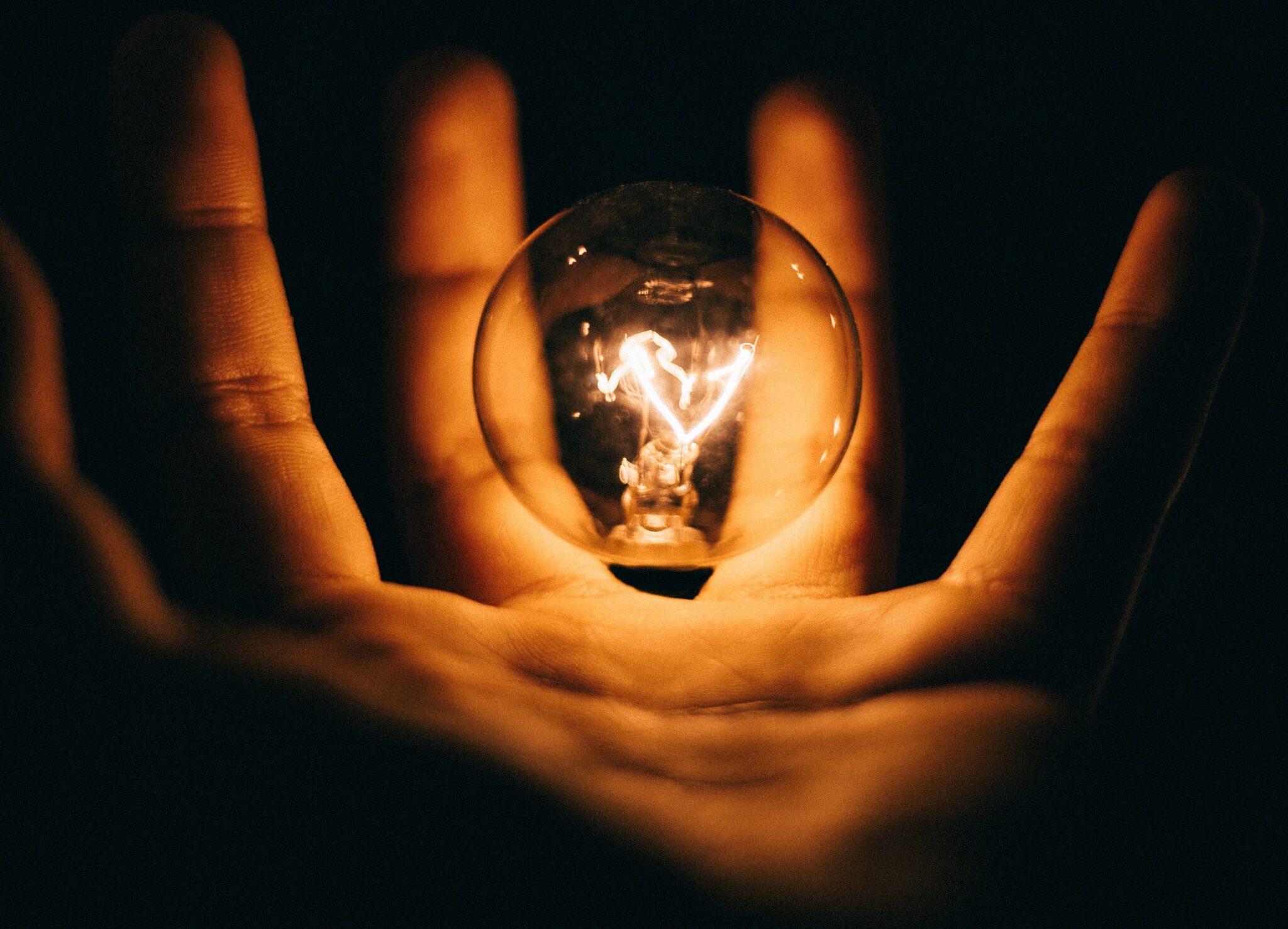 leuchtende Glühbirne in einer Hand