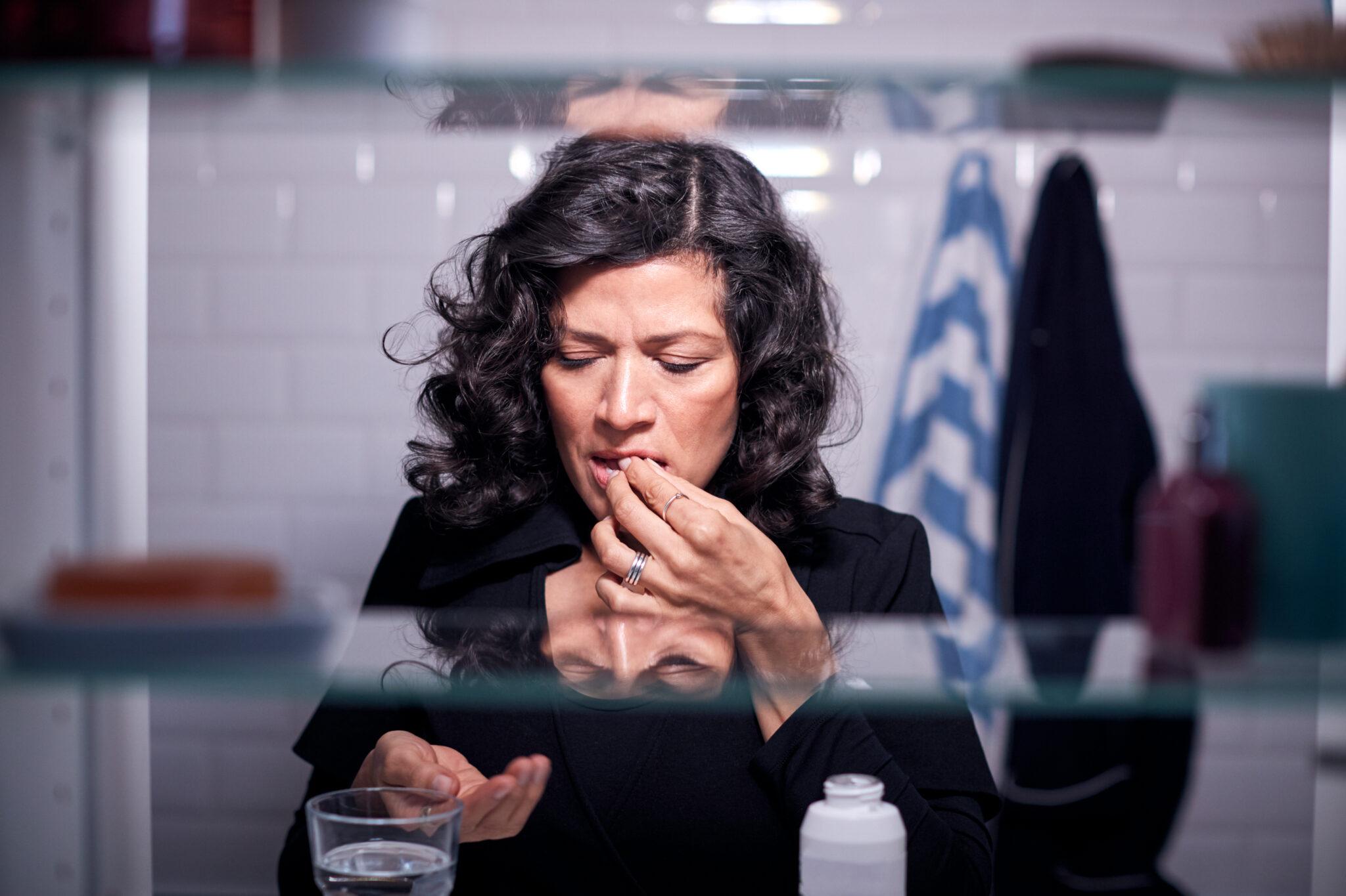 Eine Frau steht vor dem Badezimmerspiegel und nimmt eine Tablette ein.