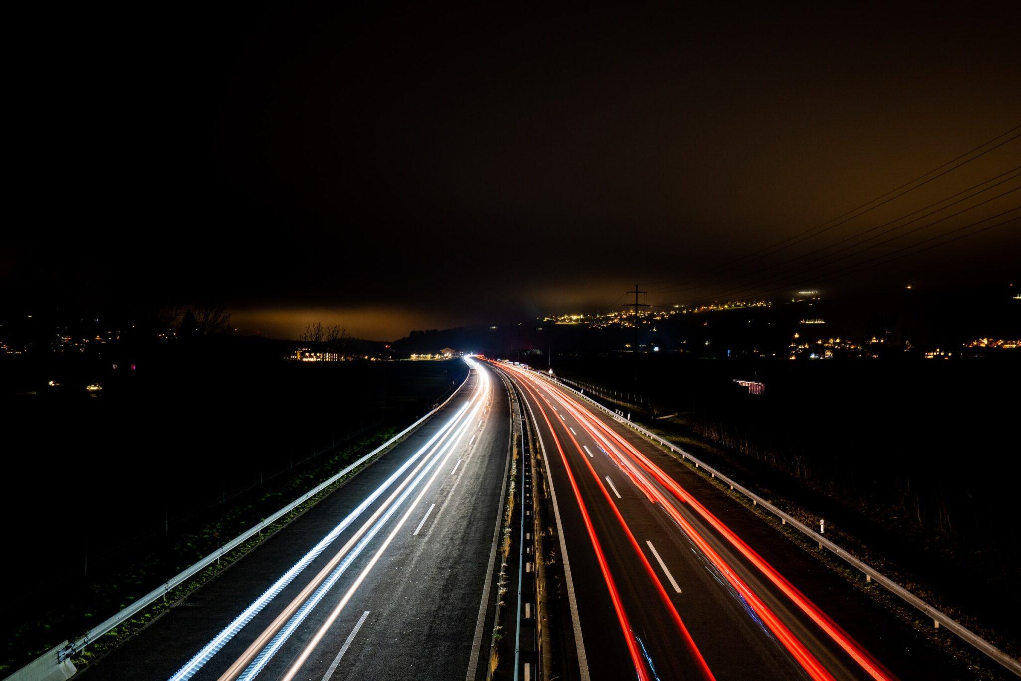 Nächtliche Strasse mit Lichtspuren der Autos von einer Brücke aus betrachtet
