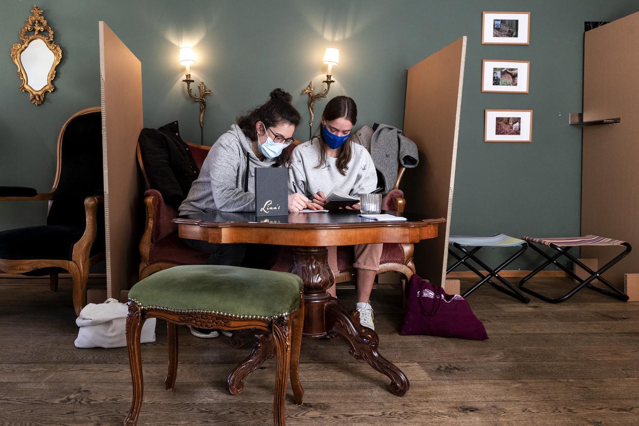 Frauen mit Hygienemaske an einem Tisch in einem Cafe
