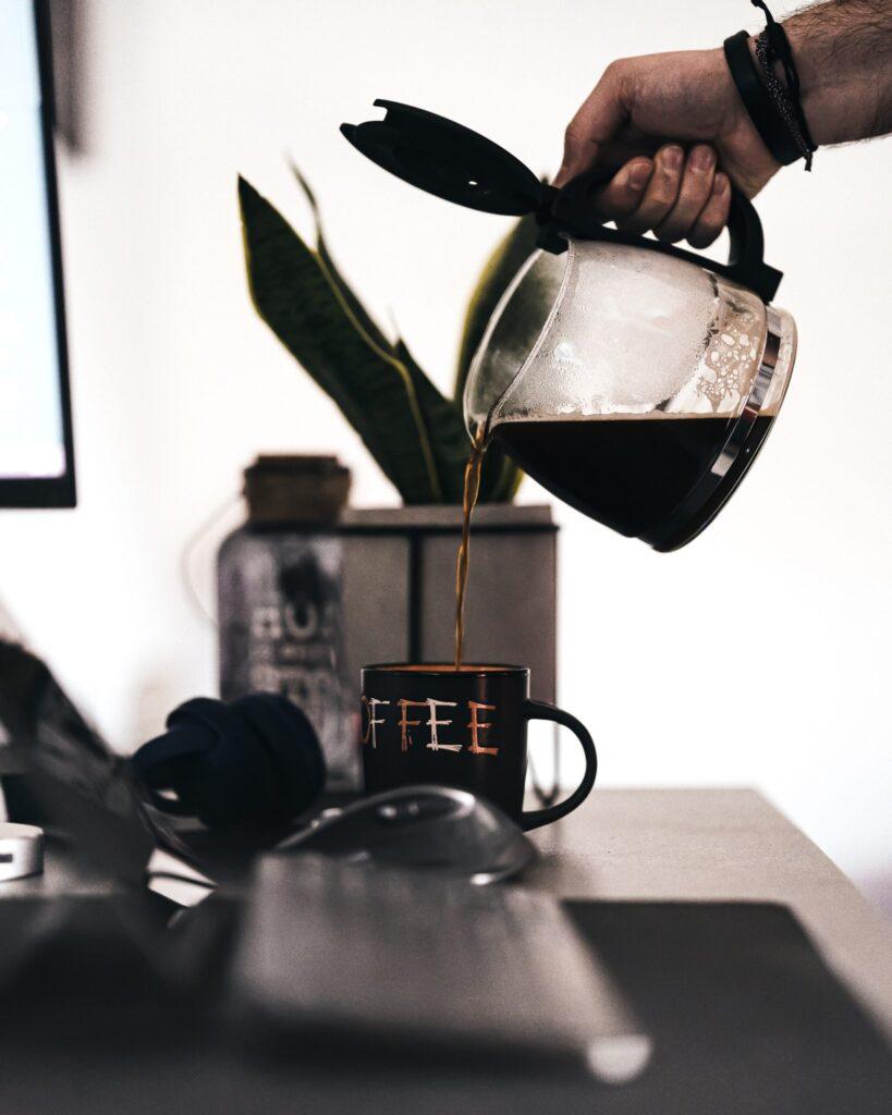 Mann giesst Filterkaffee in eine Tasse