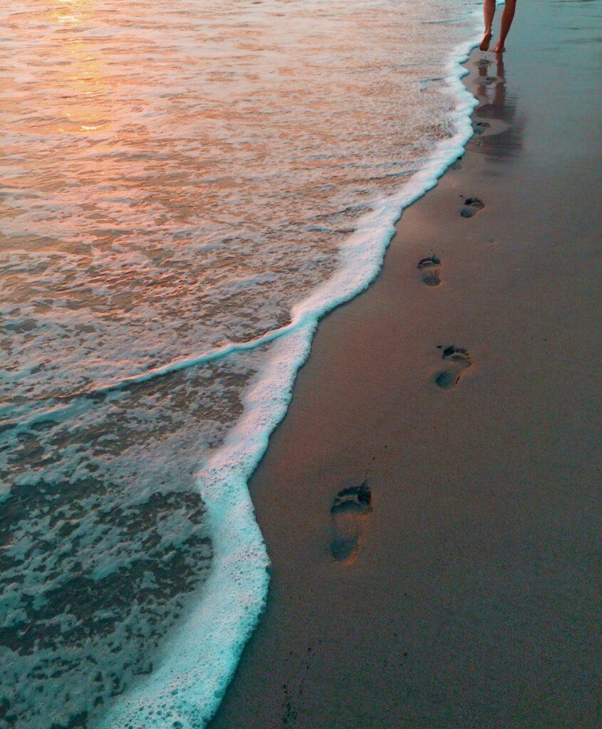 Fusspuren an einem Strand im Sonnenuntergang