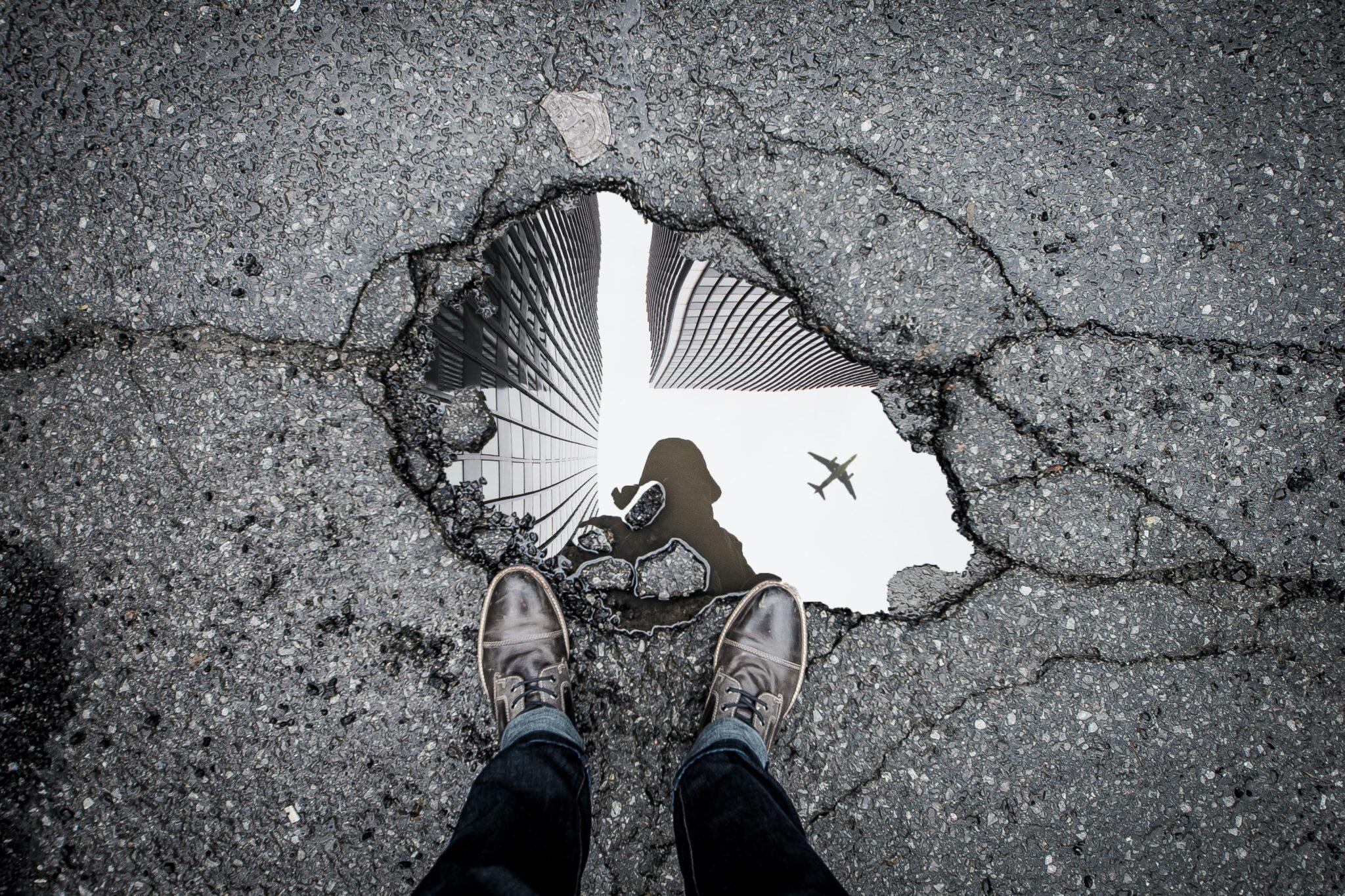 Spiegelung in einer Pfütze mit Flugzeug im Hintergrund