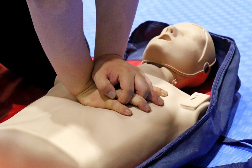 Herzdruckmassage an einer Übungspuppe