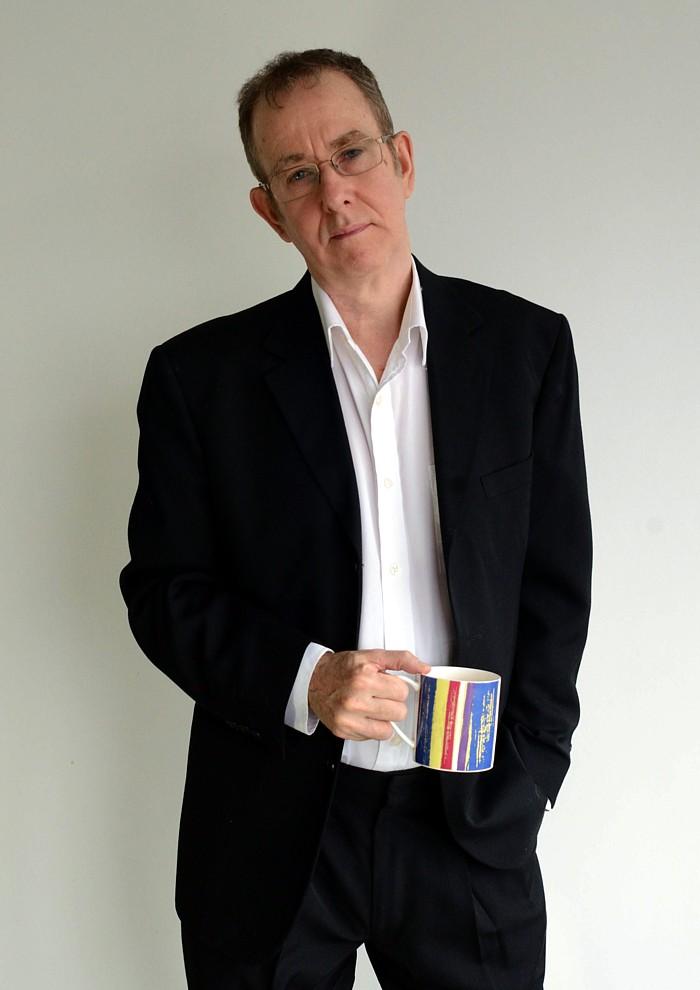 Brian Deer im Anzug mit bunter Kaffeetasse in der Hand