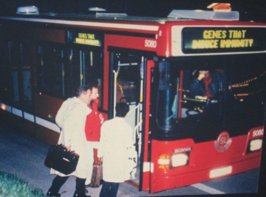 """3 Leute steigen in einen Bus ein, auf dessen Display steht """"Genes that induce immunity"""""""