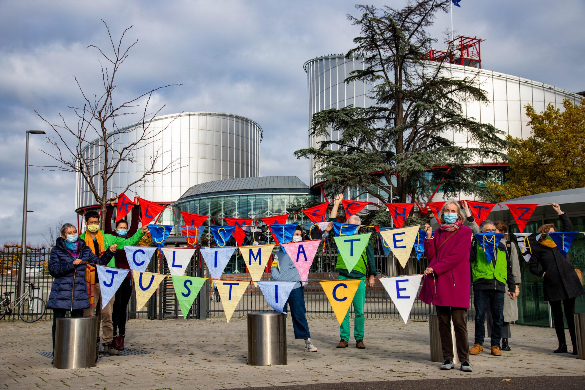 Die KlimaSeniorinnen mit bunten Wimpeln auf denen Climate Justice und Klimaschutz steht (1 Buchstabe pro Wimpel)