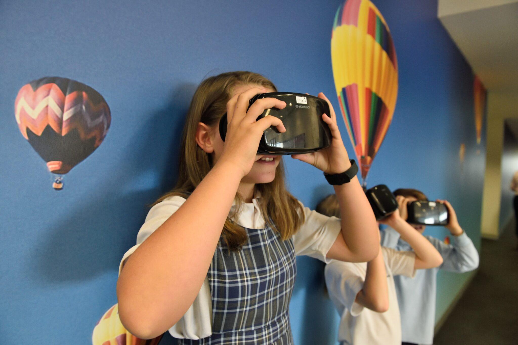 Schulkinder mit VR-Brillen vor einer Wand mit Heissluftballons