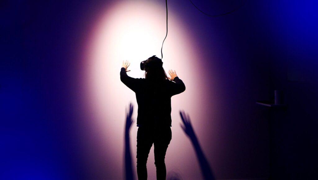 Ein mensch mit VR-Brille vor einer hellen Wand im Scheinwerferlicht