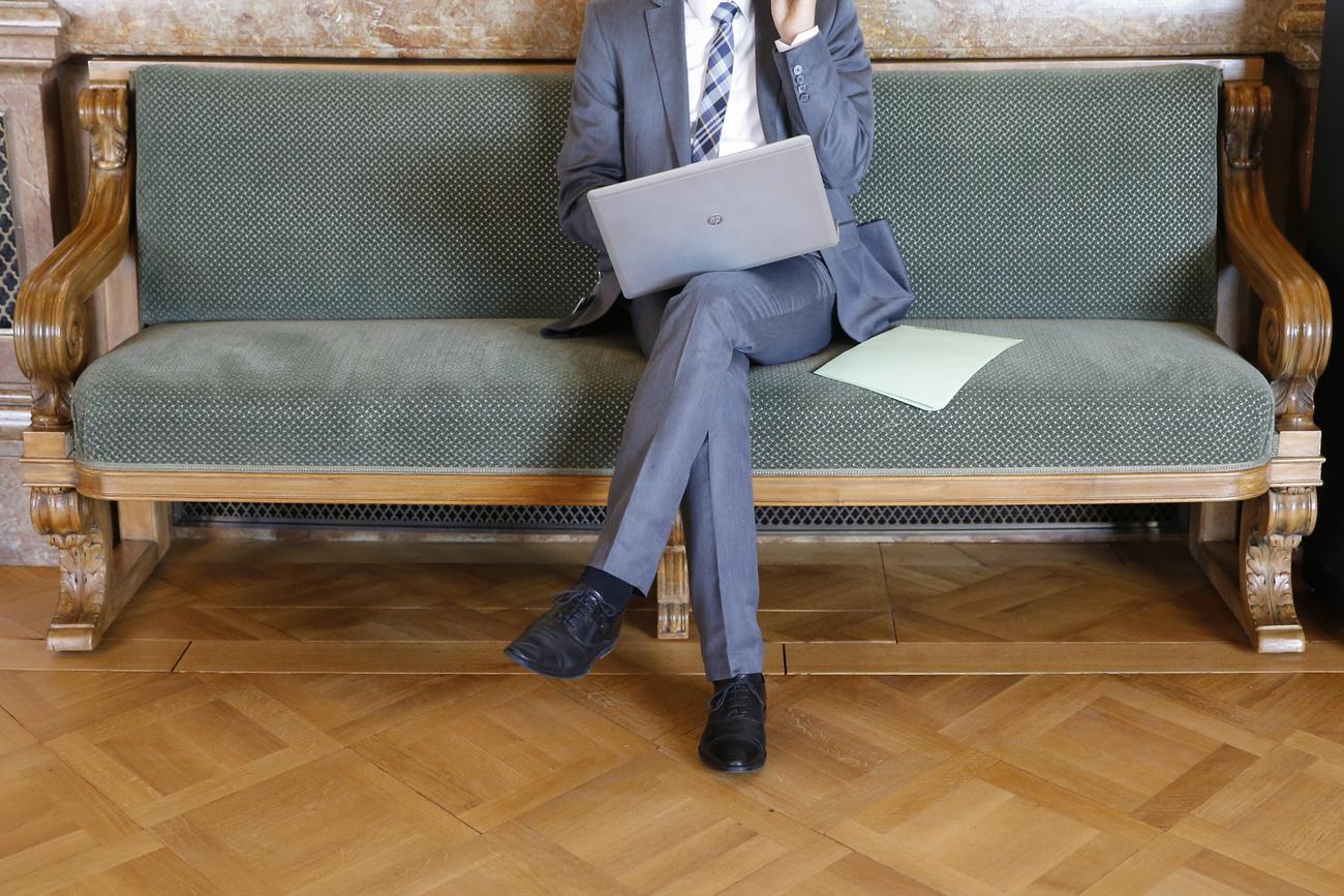 Ein Lobbyist mit Macbook sitzt in der Wandelhalle des Bundeshauses.