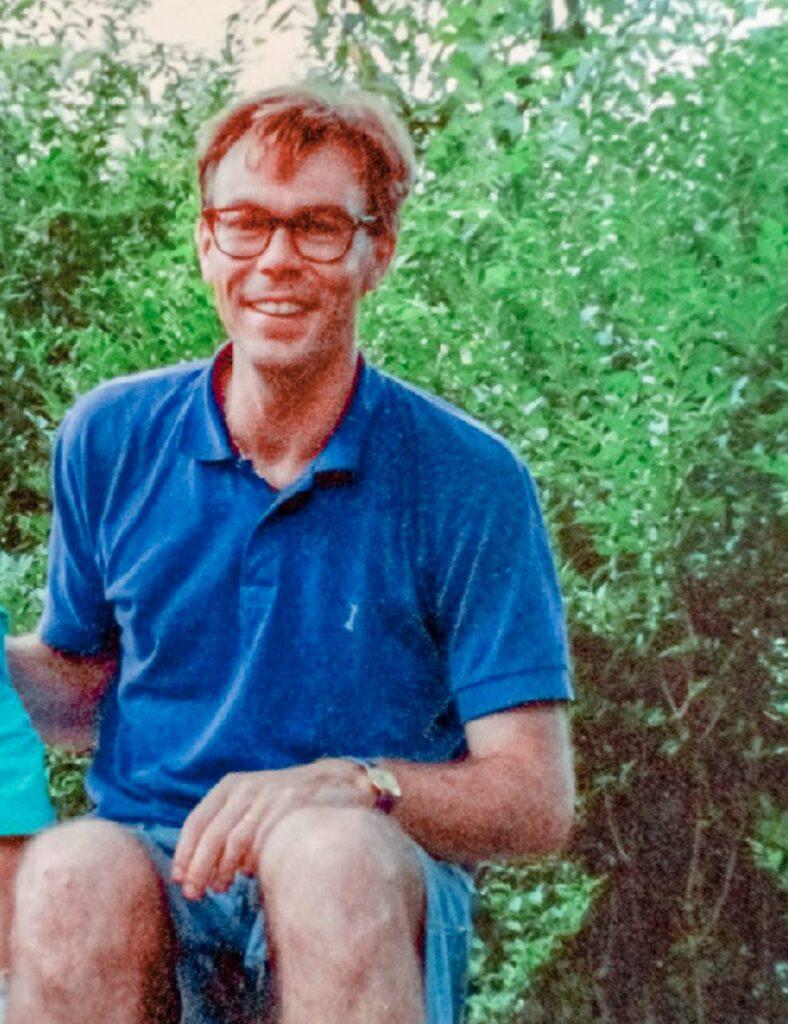 Blonder Mann mit Brille und blauem Polohemd