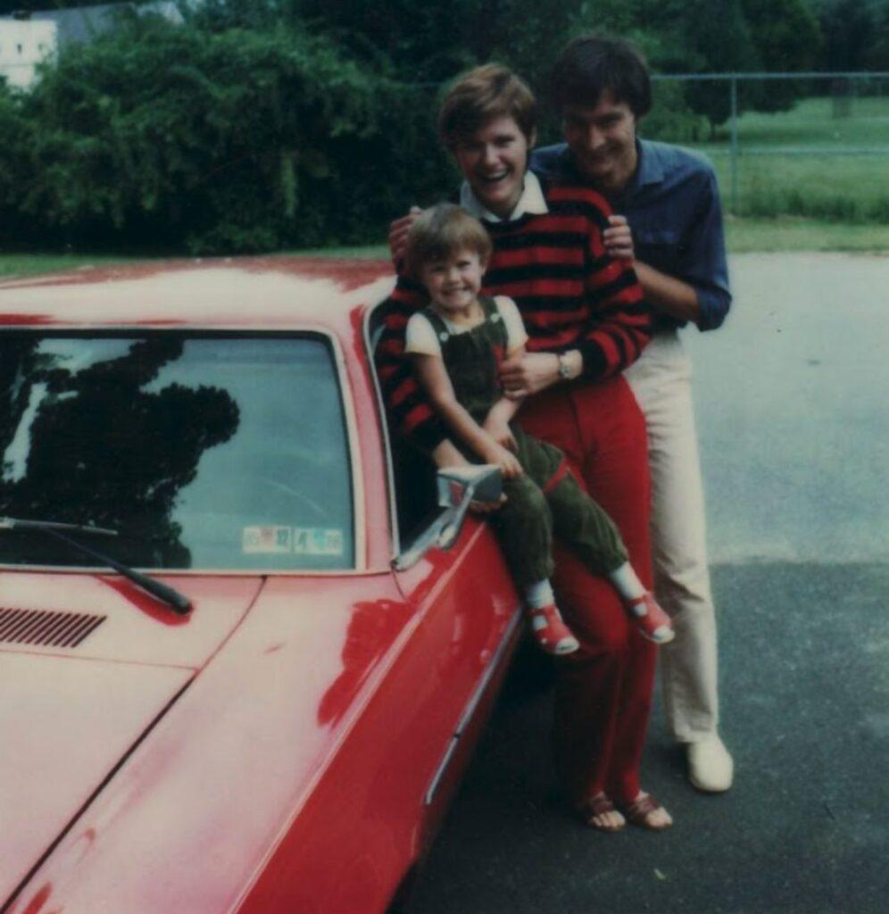 Familie lachend an ein rotes Auto gelehnt.