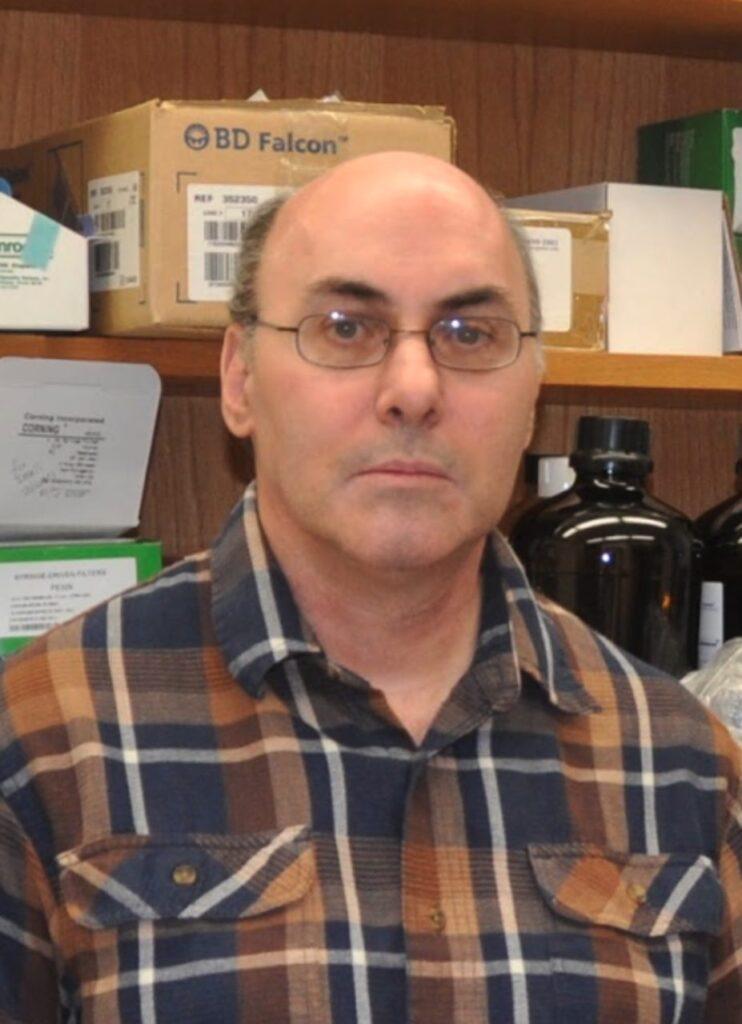 Mann mit Halbglatze und Brille vor einem Labor-Regal