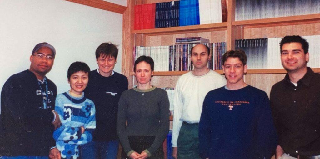 Gruppe junger Wissenschaftler und Wissenschaftlerinnen vor einem Bücherregal