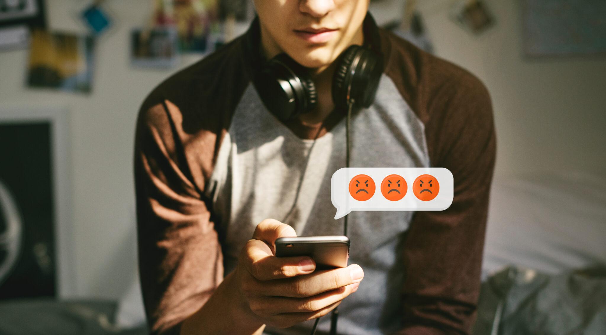 Ein junger Mann mit Handy in der Hand, über dem wütende Emoticons schweben.