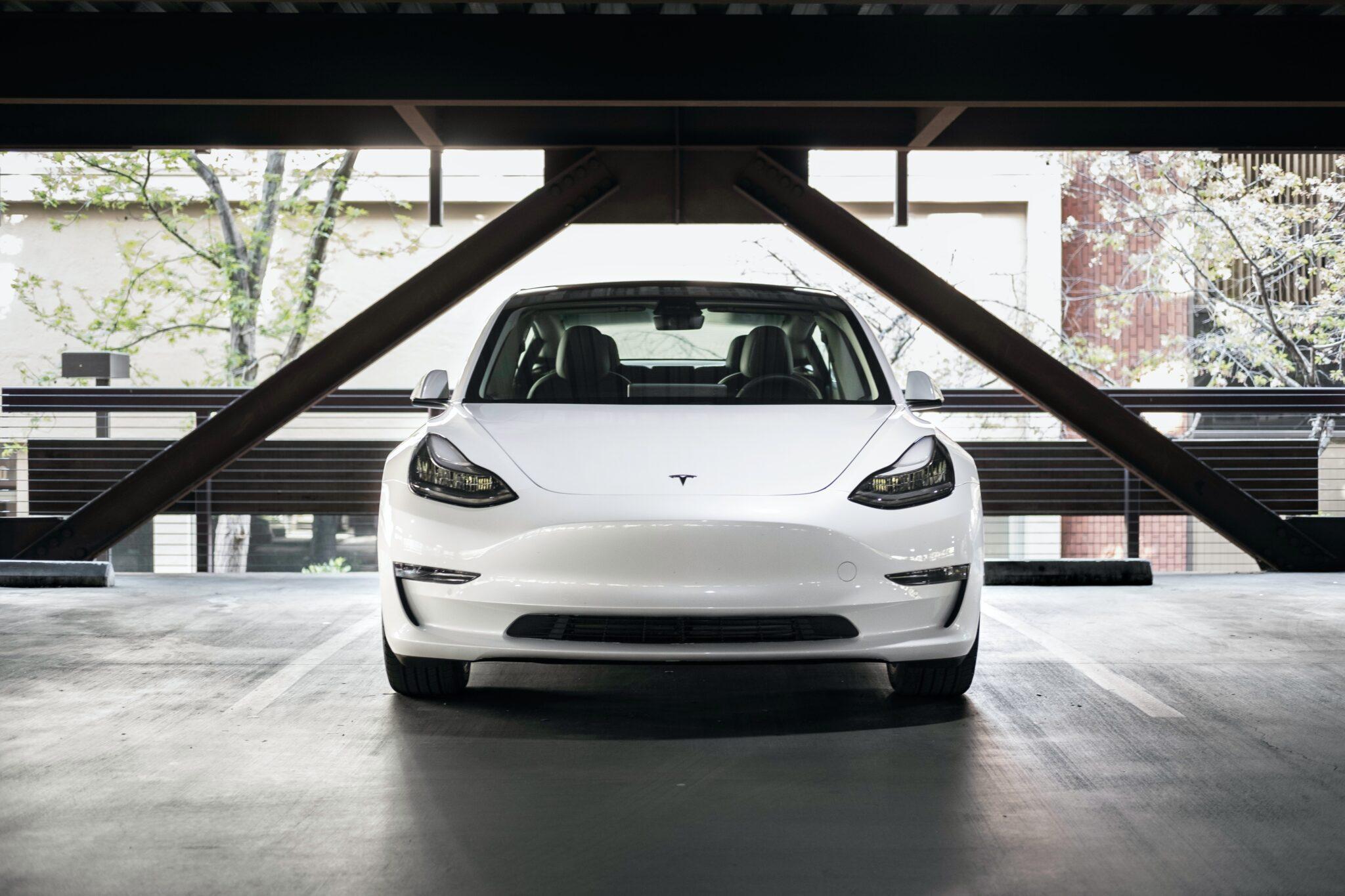 Weisser Tesla von vorne betrachtet in einem Parkhaus