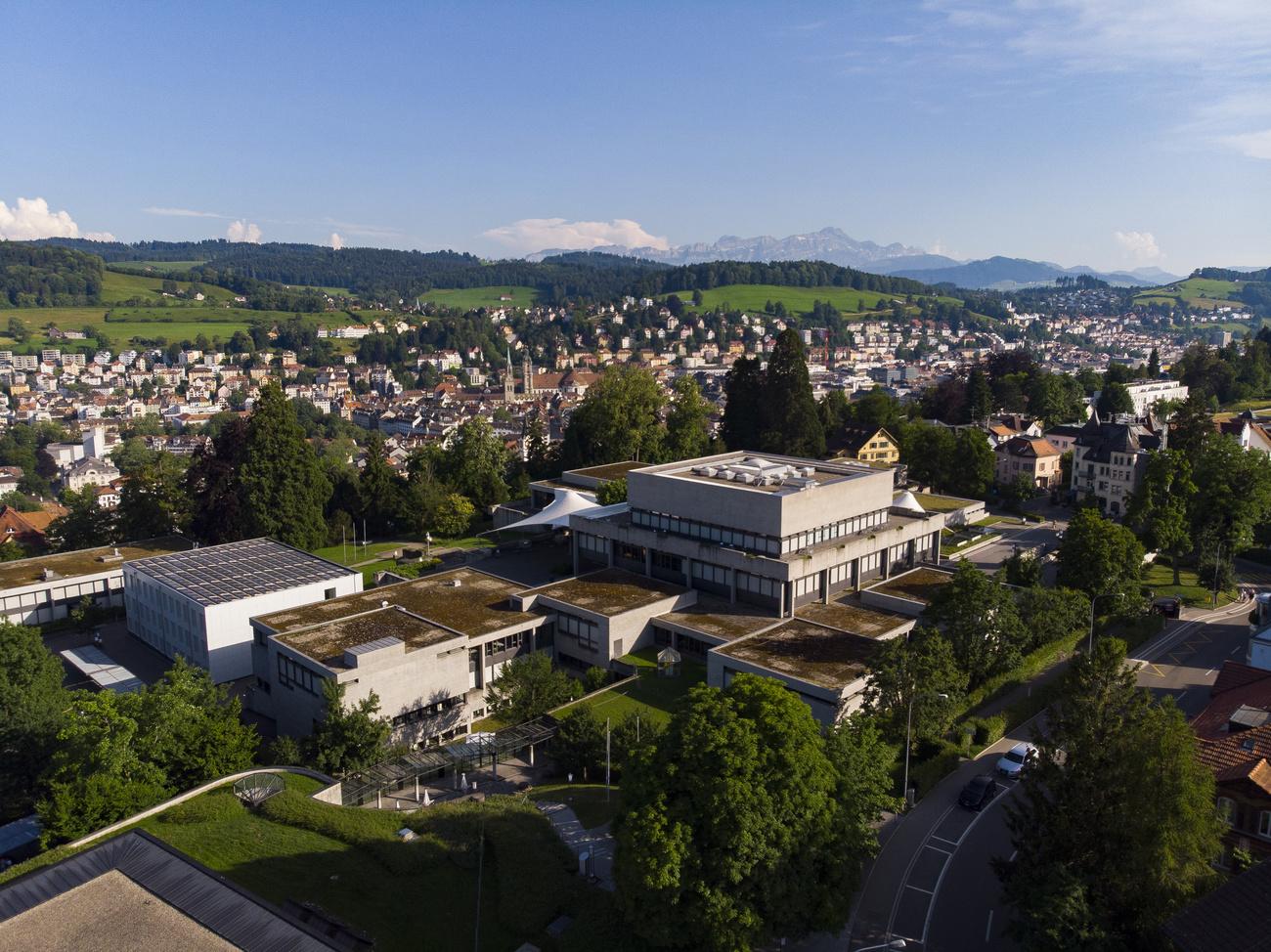 Campus der Uni St. Gallen von oben aufgenommen mit St. Gallen, Wiesen und Bergen im Hintergrund.