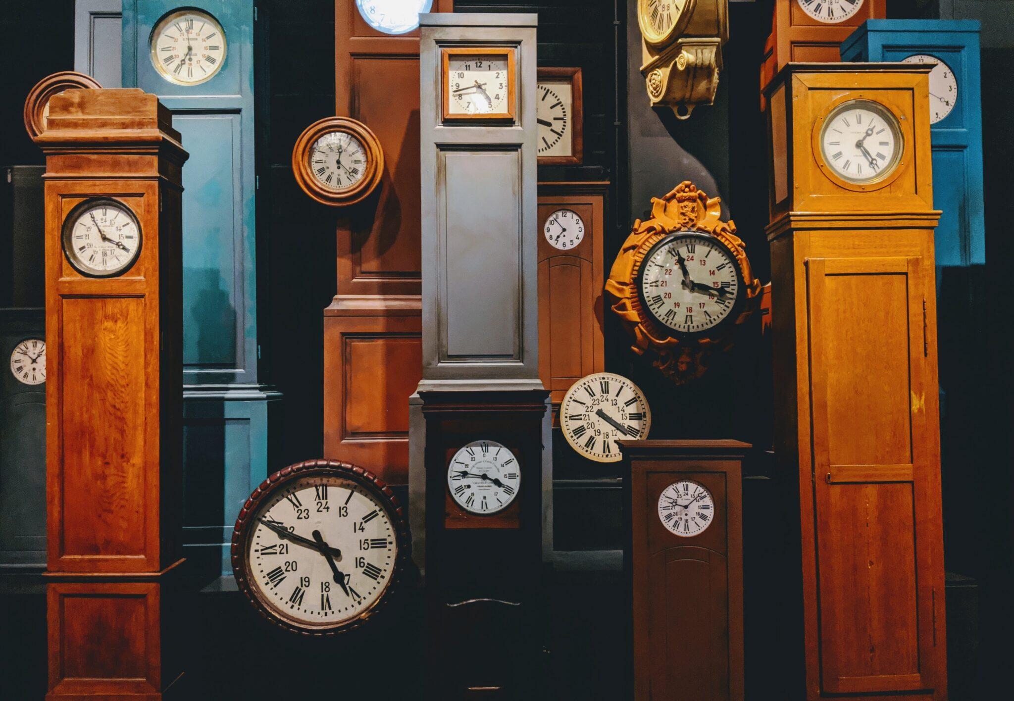 Verschiedene Standuhren und Ziffernblätter mit unterschiedlichen Uhrzeiten