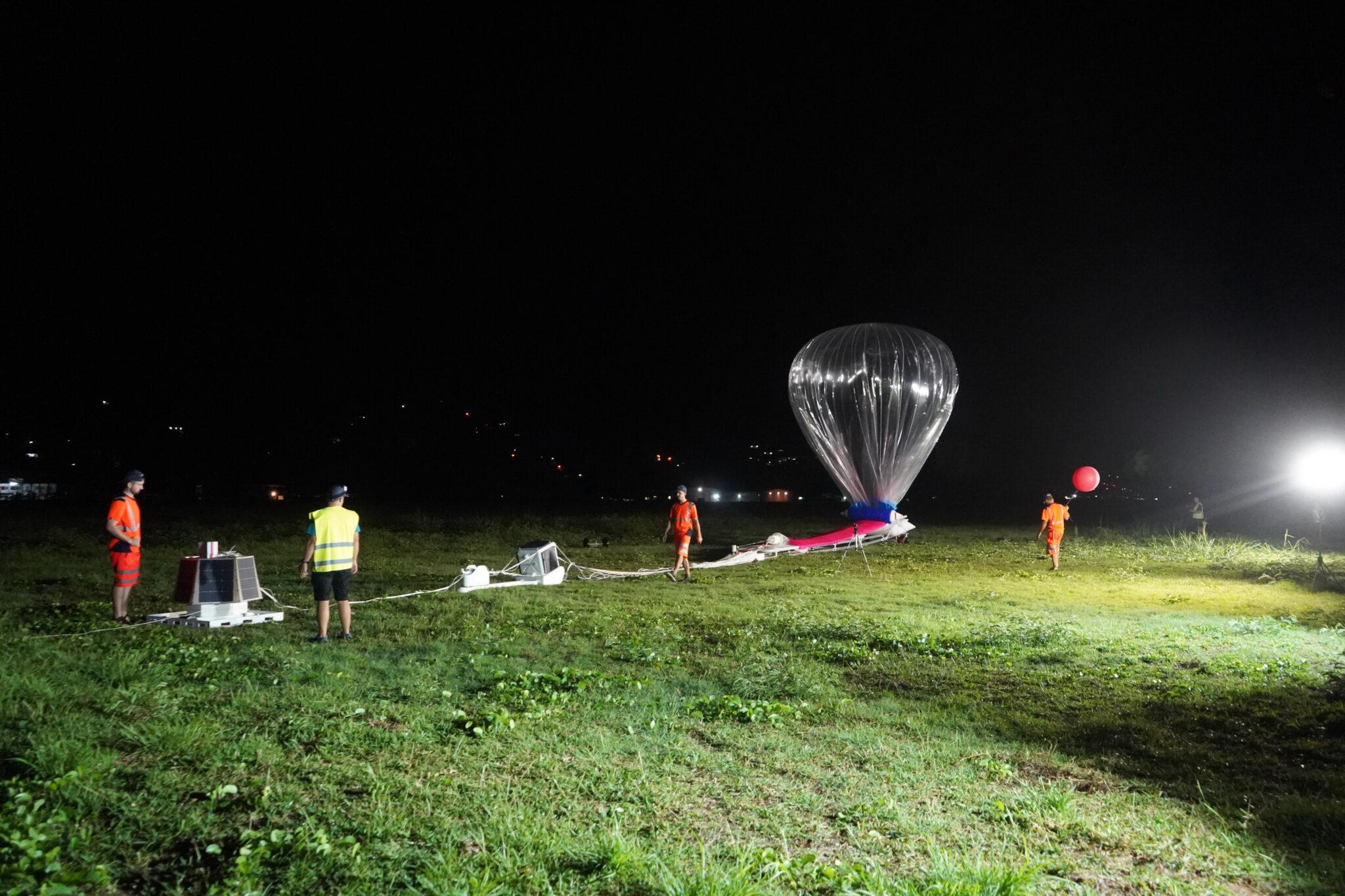 Ein durchsichtiger grosser Ballon nachts auf einer Wiese.