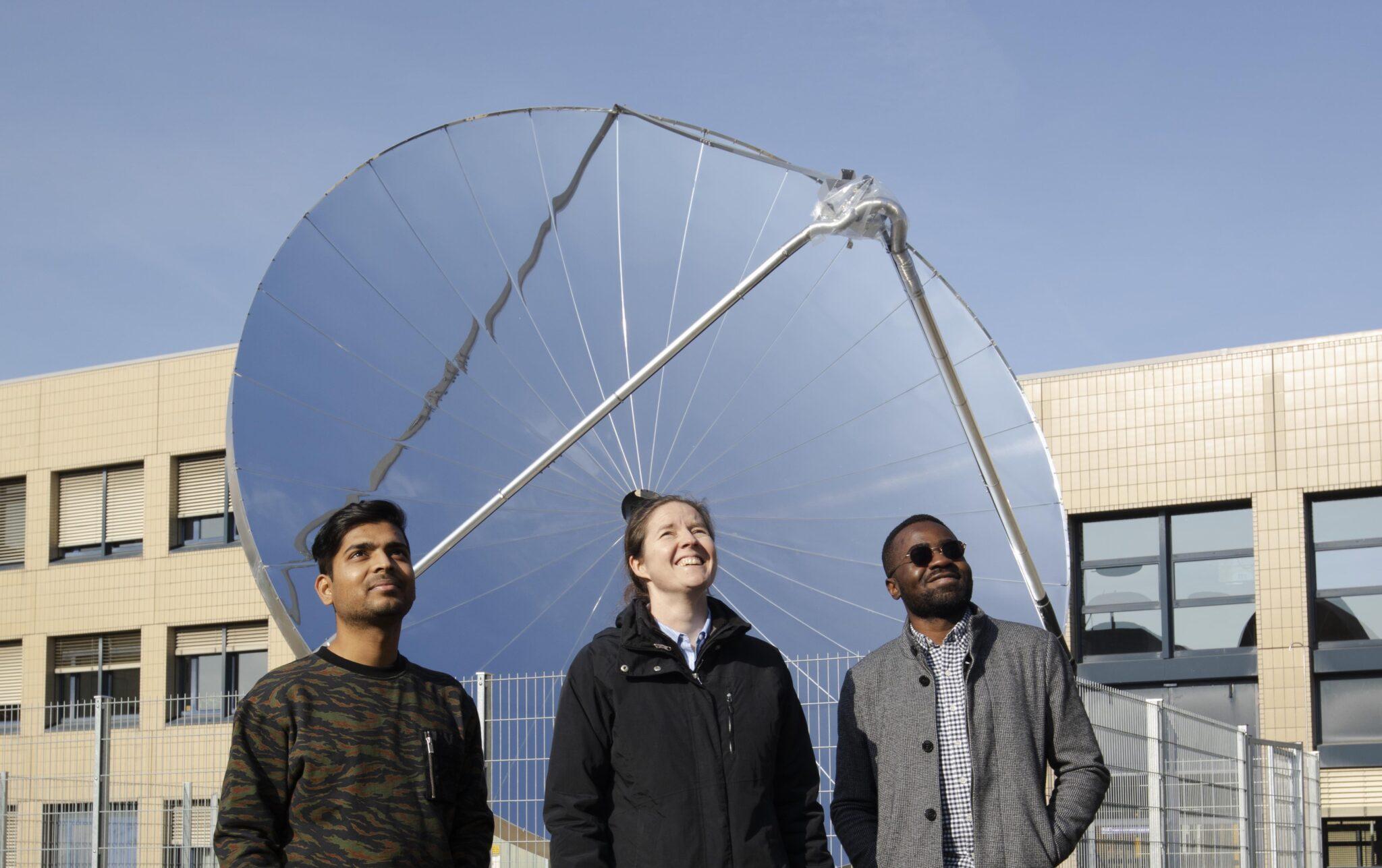 Eine Forscherin und 2 Forscher vor einem Parabolspiegel.