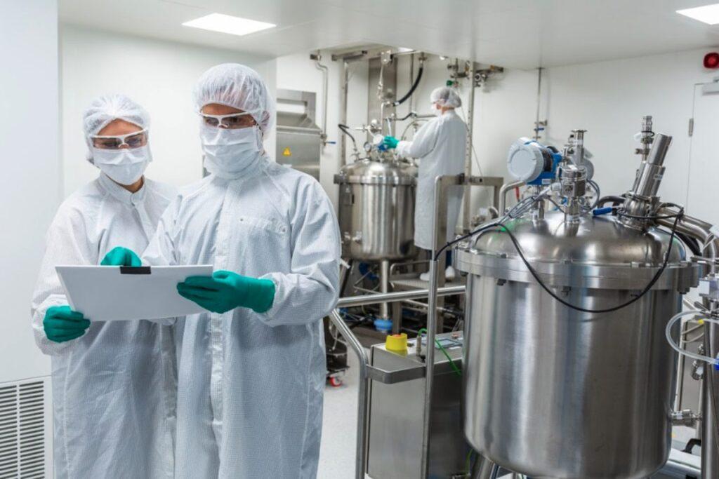 2 Wissenschaftler in weissen Ganzkörperschutzanzügen vor mehreren Stahlbehältern im Labor