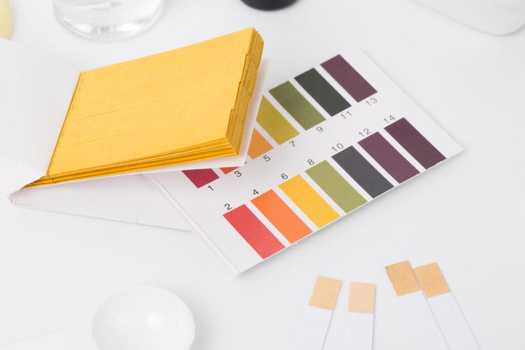 Ph-Teststreifen mit Farbtabelle Rot bis gelb = sauer. Grün, blau und violett sind basisch.