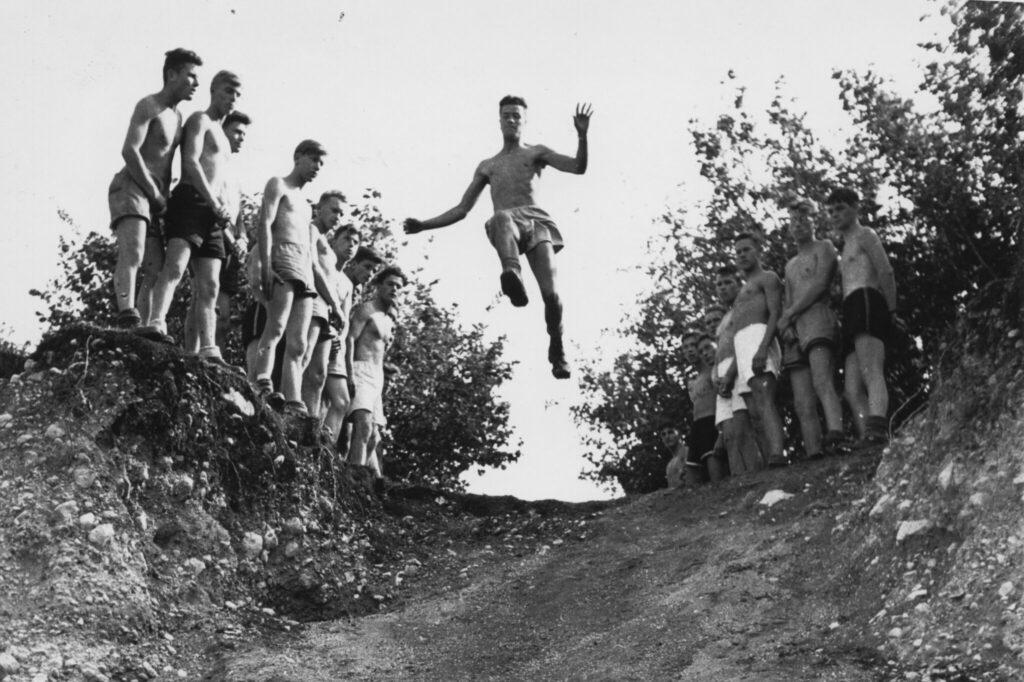 Schwarzweiss Bild von Männern, die in eine Kiesgrube springen, von unten aufgenommen.