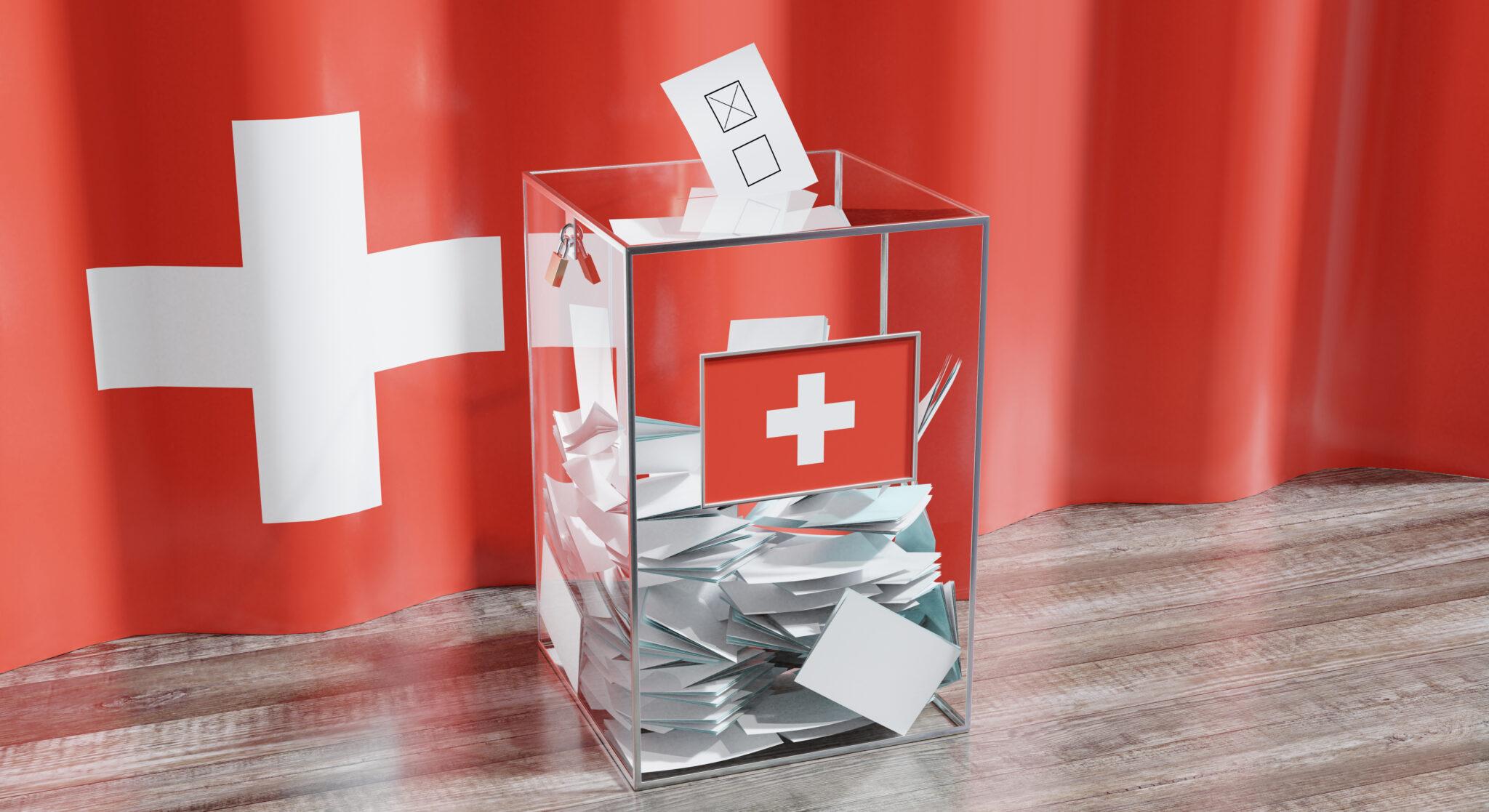durchsichtige Wahlurne mit Schweizer Flagge.