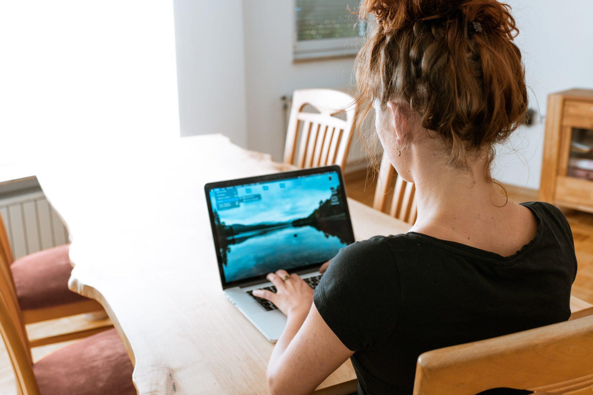 Eine Frau sitzt am Laptop arbeitend an einem Küchentisch