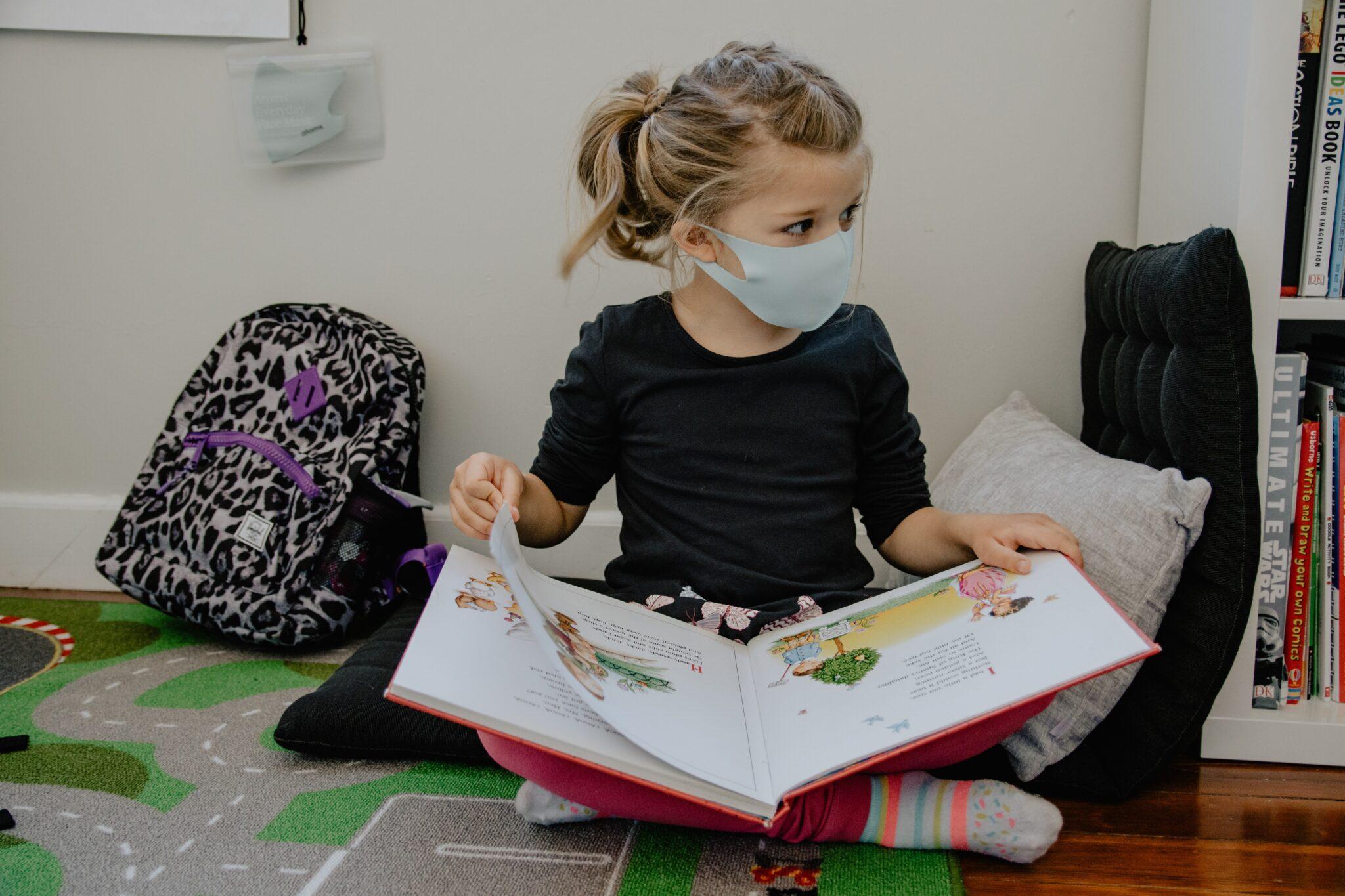Ein Mädchen im Grundschulalter sitzt mit Mundnasenschutzmaske auf dem Boden und schaut sich ein grosses Buch an