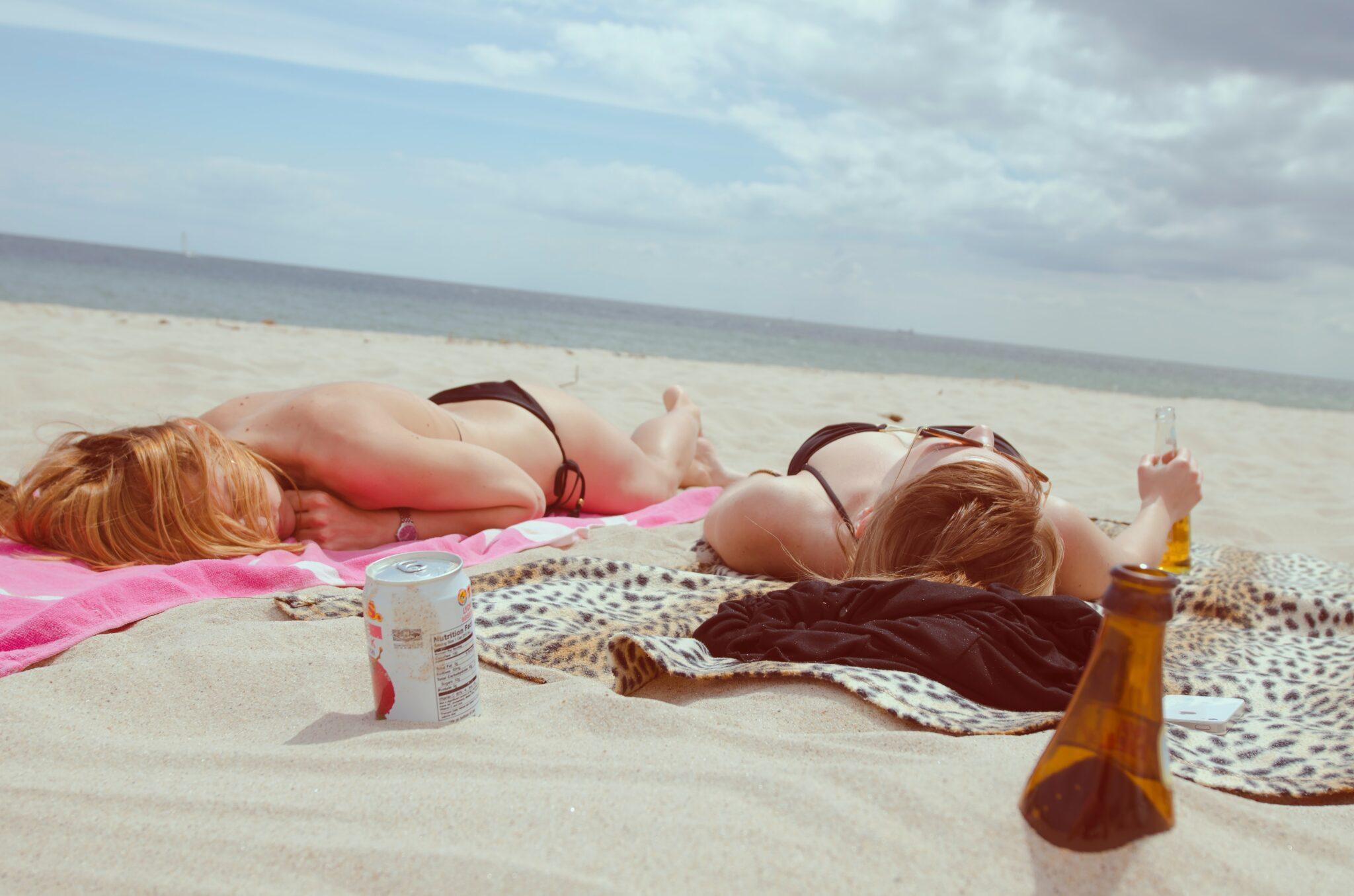 Zwei Frauen in Bikini liegen an einem Sandstrand, die Sonne scheint.